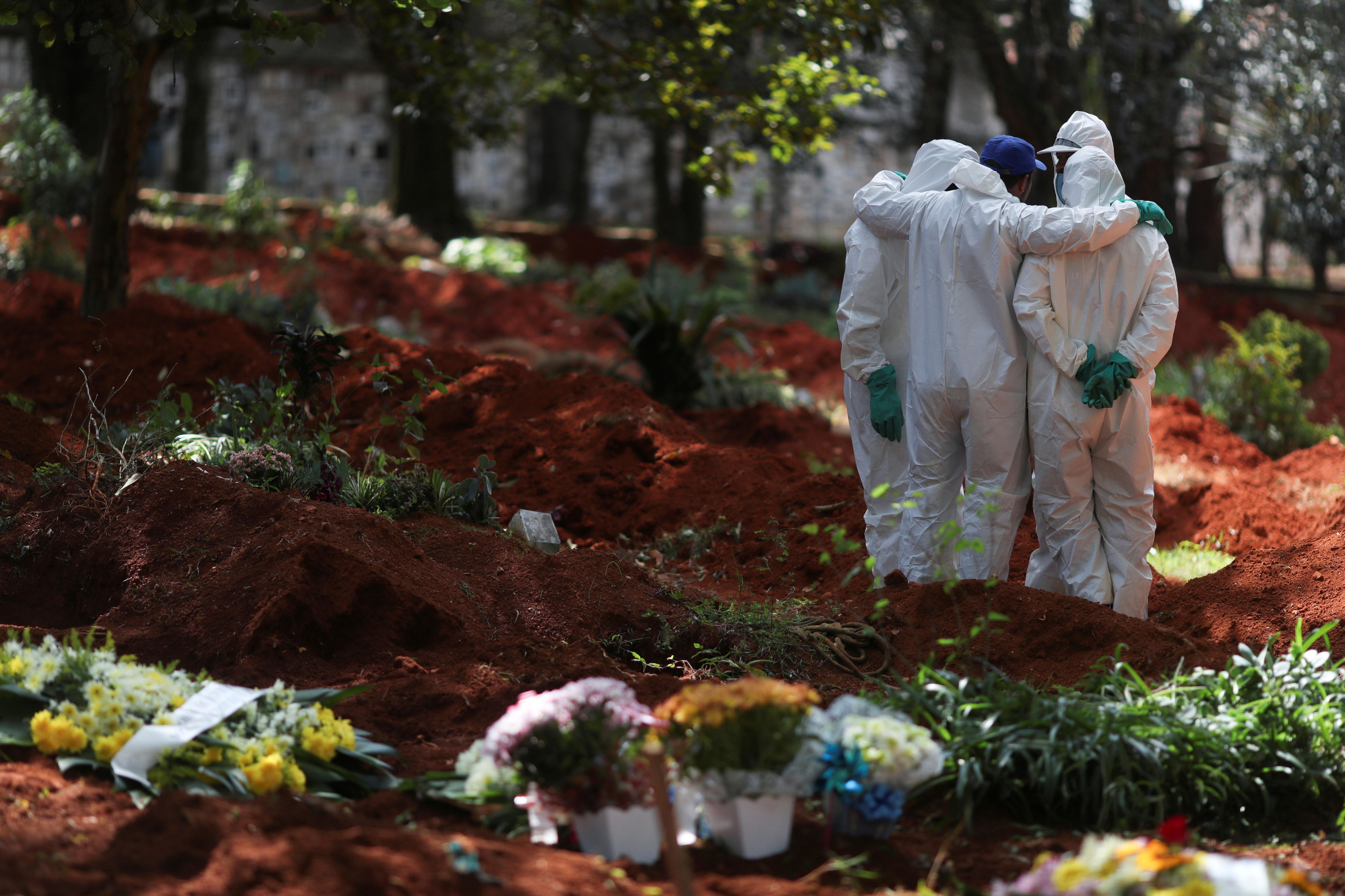 Sepultureros con trajes protectores se reúnen en el cementerio de Vila Formosa durante el brote de la enfermedad por coronavirus con trajes especiales para protegerlos del contagio (Reuters)
