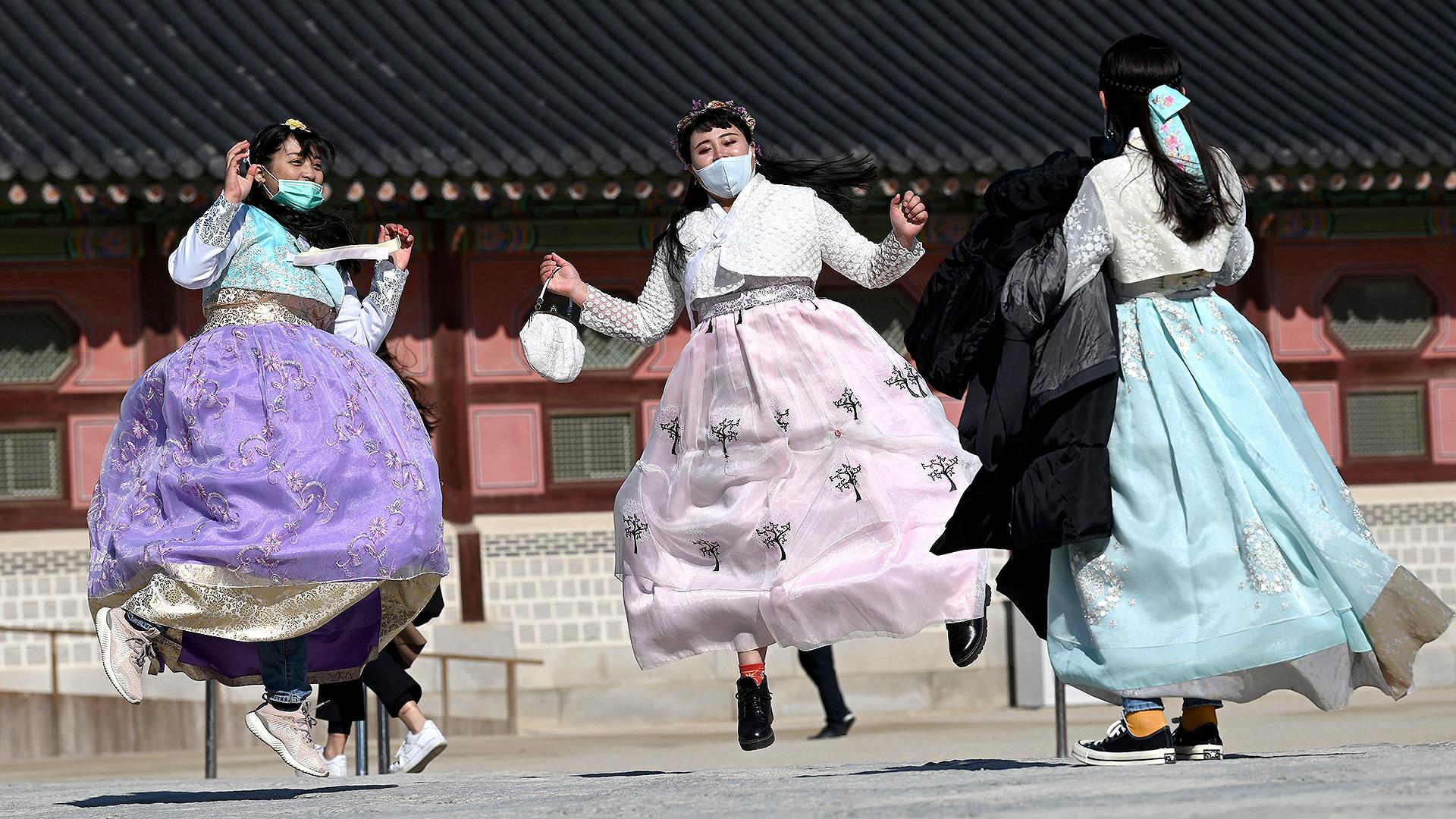 Las personas con vestidos tradicionales de hanbok coreanos usan máscaras faciales mientras saltan para una foto de recuerdo en el palacio Gyeongbokgung en Seúl el 3 de febrero de 2020 (Jung Yeon-je / AFP)