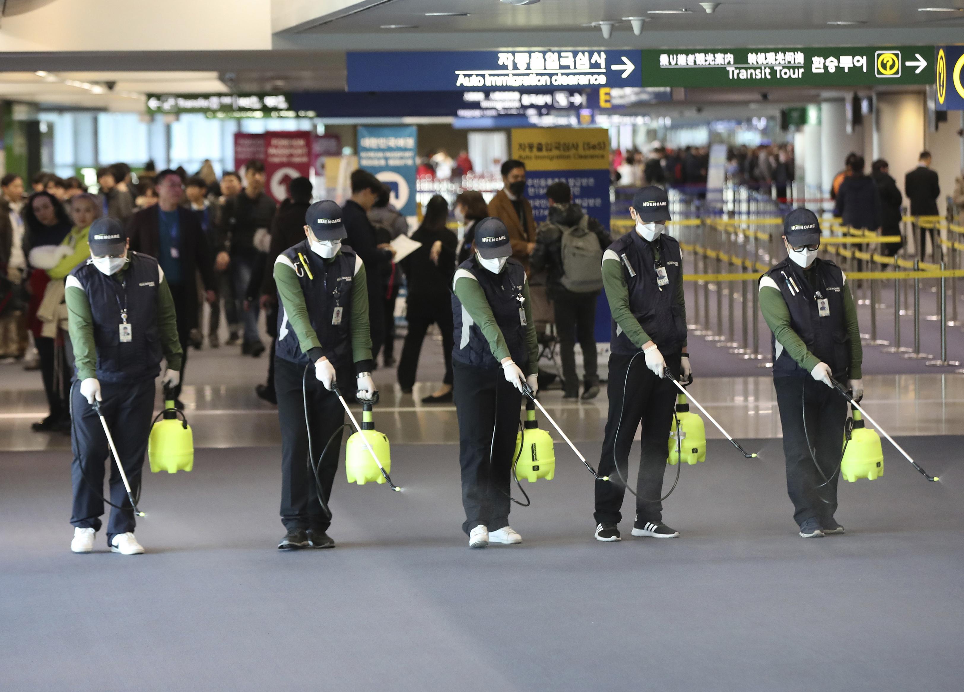 Los trabajadores rocían una solución antiséptica en el vestíbulo de llegadas en medio de las crecientes preocupaciones del público sobre la posible propagación de un nuevo coronavirus en el Aeropuerto Internacional de Incheon en Incheon, Corea del Sur, el martes 21 de enero de 2020. Se tomaron mayores precauciones en China y en otros lugares el martes como gobiernos se esforzó por controlar el brote de un nuevo coronavirus que amenaza con crecer durante el viaje del Año Nuevo Lunar. (Suh Myung-geon / Yonhap vía AP)