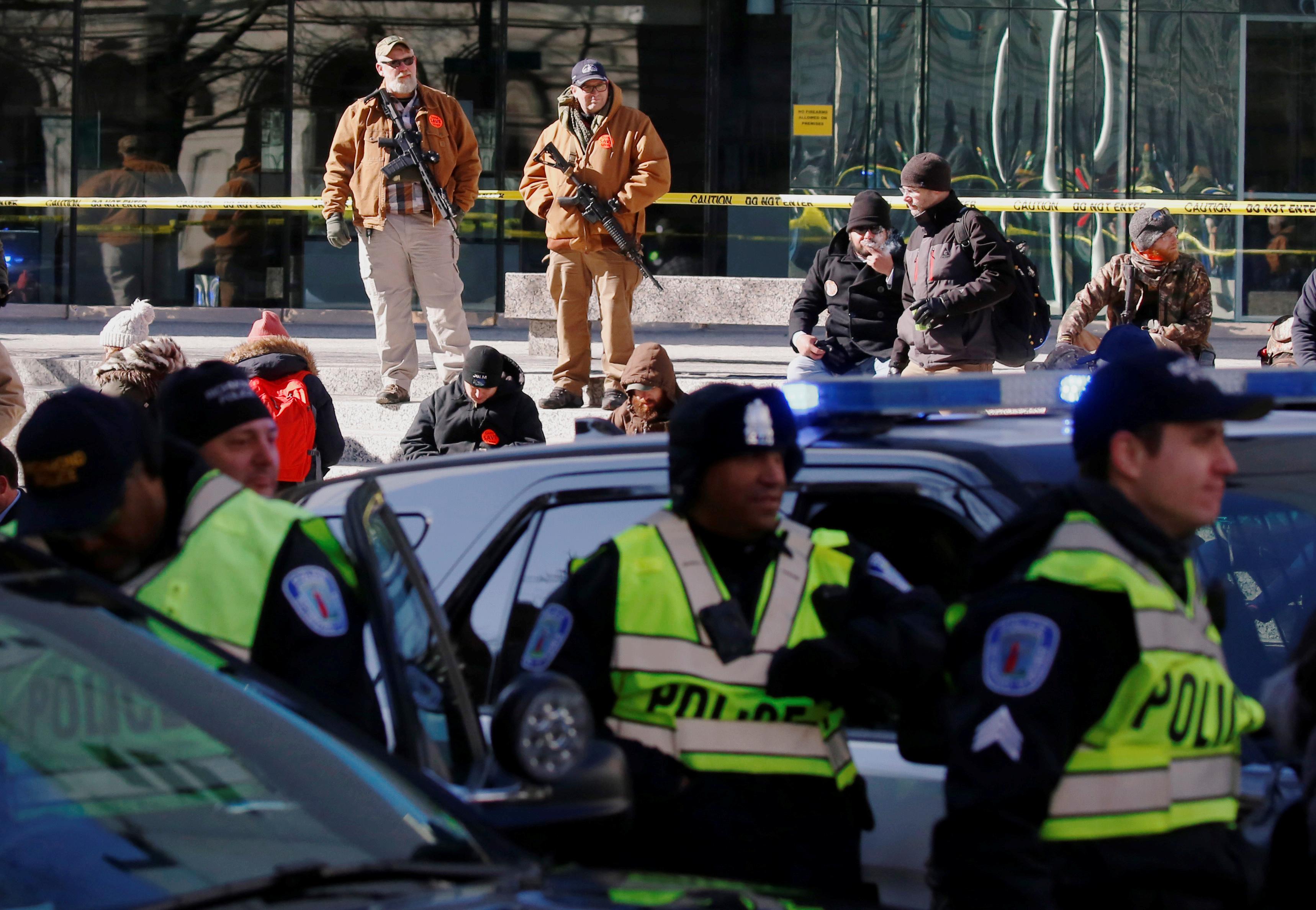 La policía custodia, en primer plano, y se asegura que no ingresen armas al sector frente al Capitolio. Por detrás, dos asistentes con sus AR-15 (REUTERS/Jim Urquhart)