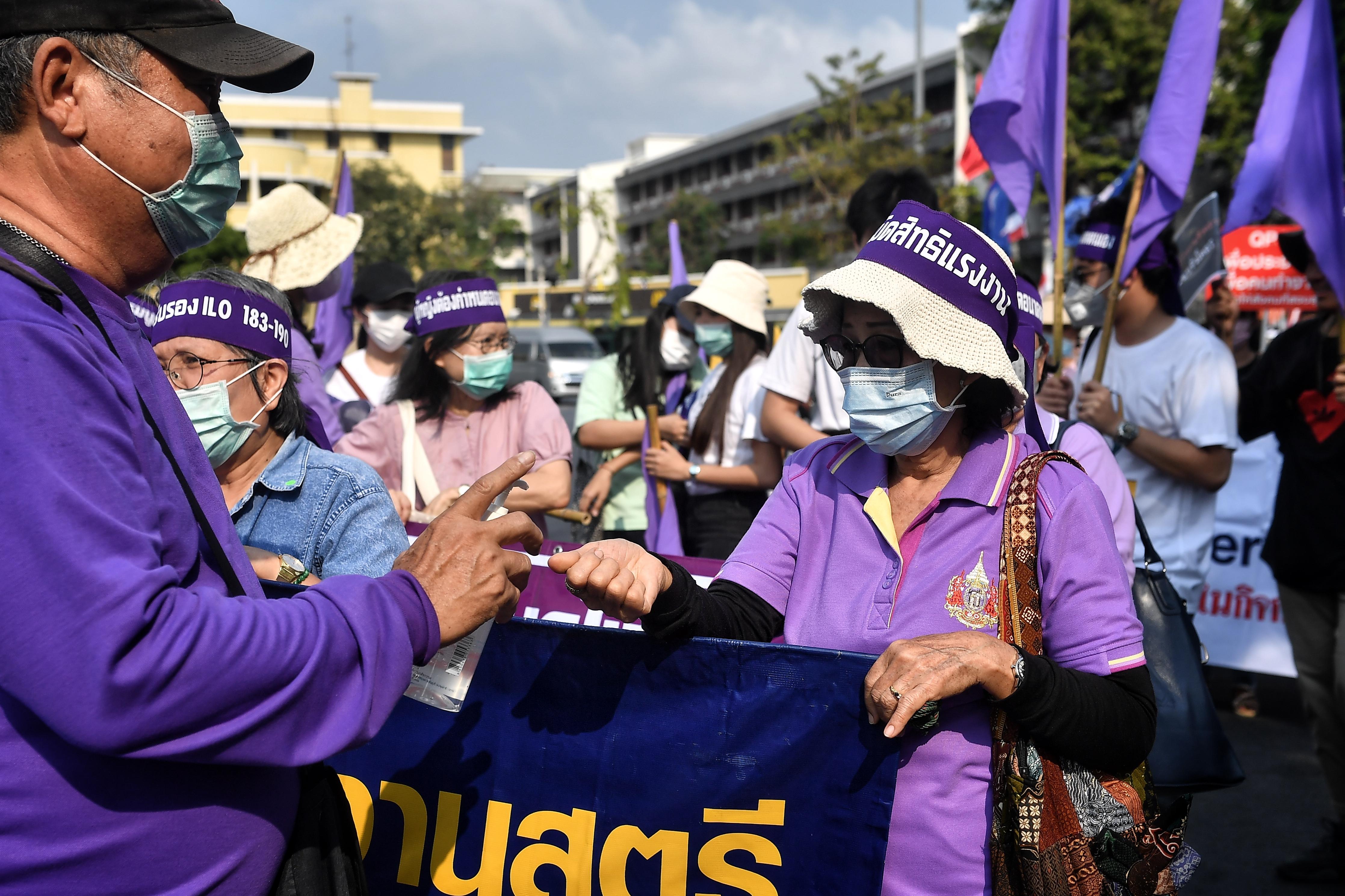 Miembros de grupos de derechos laborales tailandeses y sindicatos de empresas estatales reciben desinfectante para manos durante una marcha por los derechos laborales en el Día Internacional de la Mujer en Bangkok el 8 de marzo de 2020. (Foto de Lillian SUWANRUMPHA / AFP)
