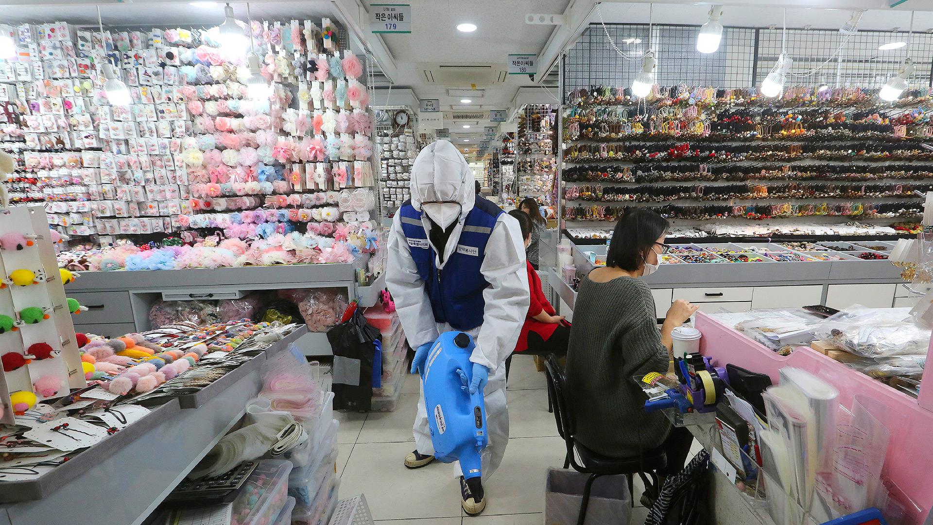 Un trabajador con engranajes protectores rocía desinfectante dentro de una tienda como medida de precaución contra un nuevo coronavirus en el mercado de Namdaemun en Seúl, Corea del Sur (AP / Ahn Young-joon)