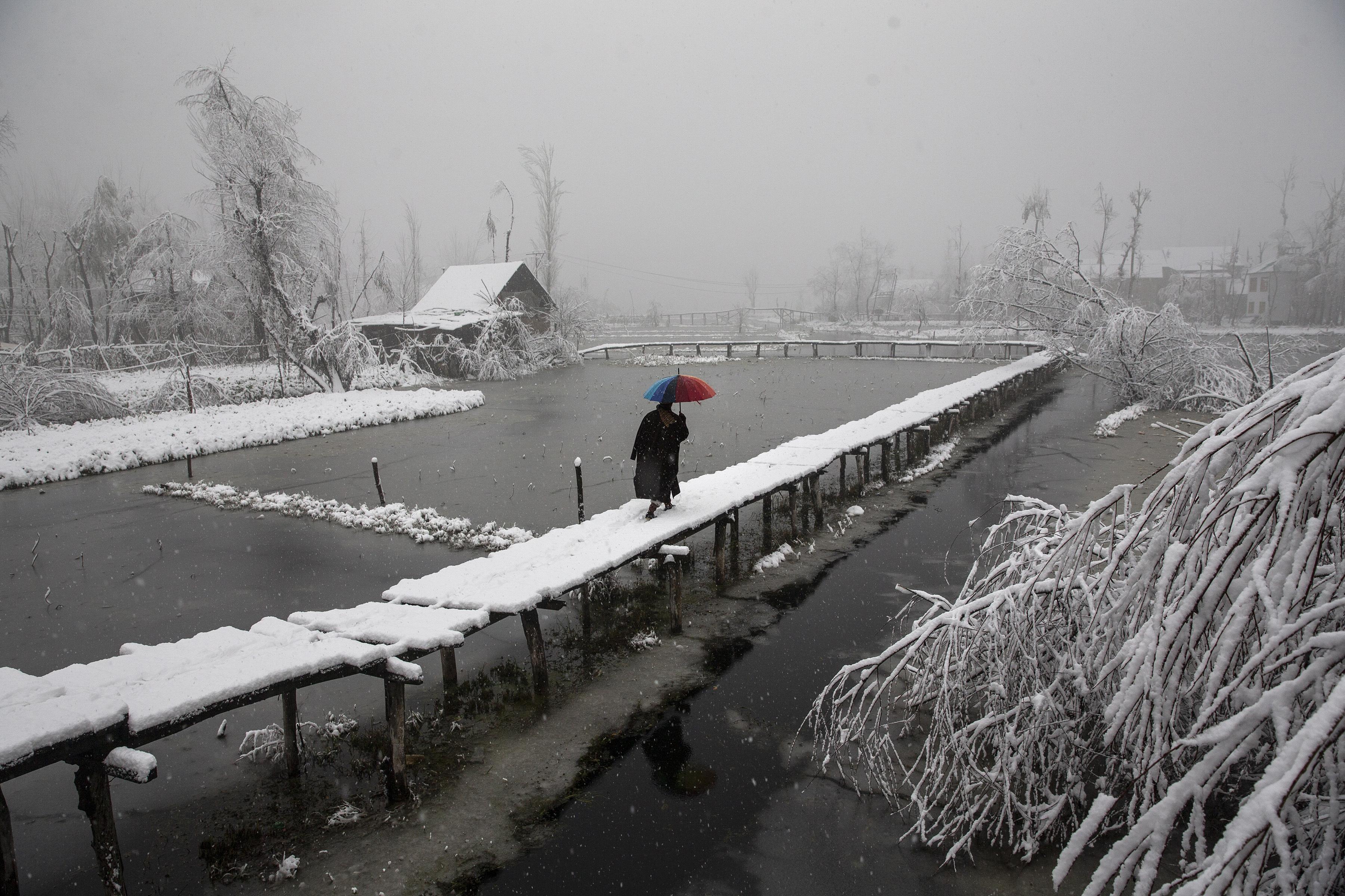 Un hombre de Cachemira camina sobre una pasarela cubierta de nieve mientras nieva en el interior del lago Dal en Srinagar, Cachemira controlada por la India, el 13 de diciembre de 2019. (Foto AP / Dar Yasin)
