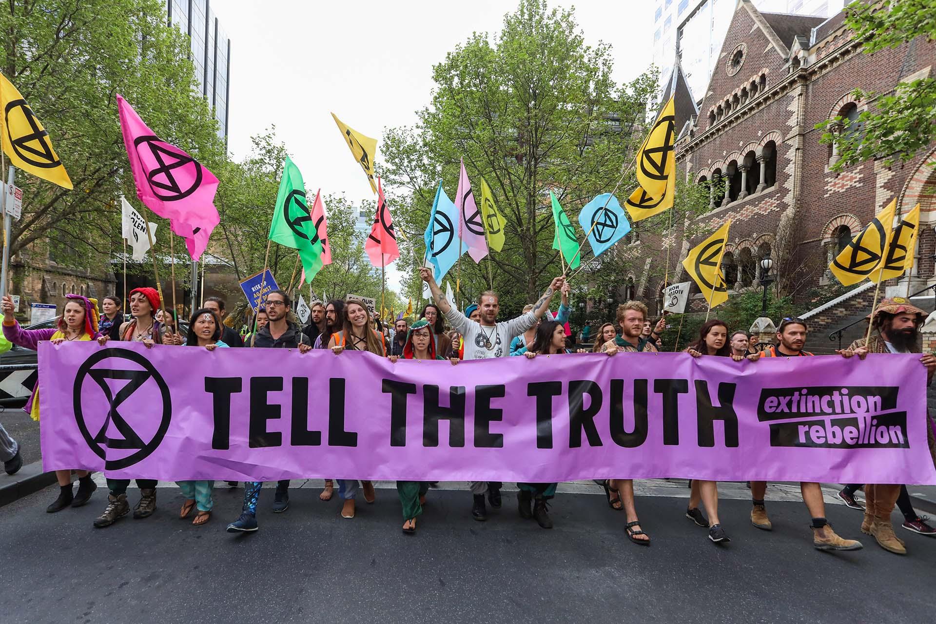 Manifestantes marchan en una calle durante una protesta de rebelión de extinción en Melbourne el 7 de octubre de 2019. (Foto de ASANKA BRENDON RATNAYAKE / AFP)