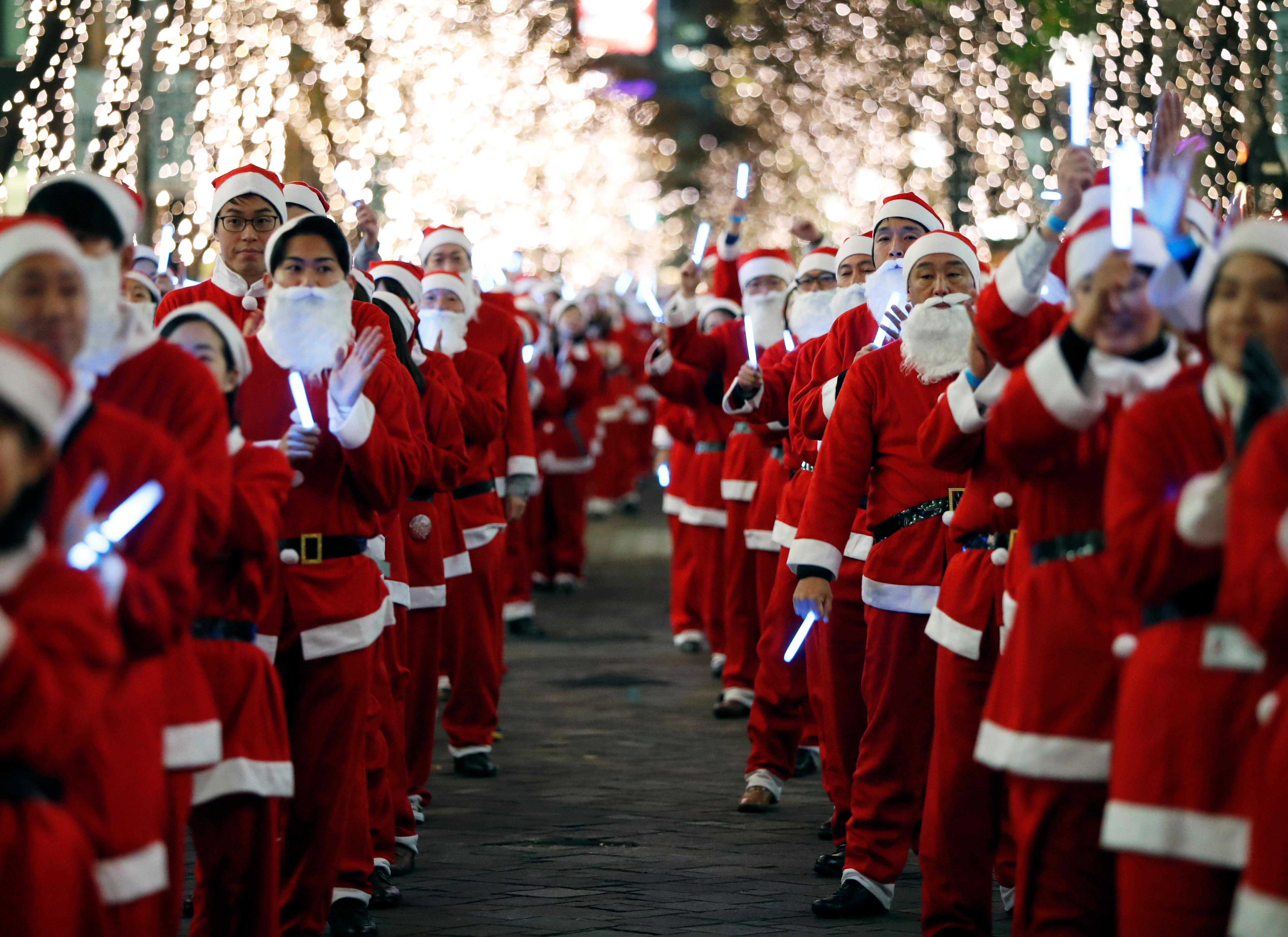 Trabajadores vestidos como Papá Noel desfilan por el distrito de negocios de Marunouchi para alentar la promoción del área, en Tokio, Japón, el 23 de diciembre de 2019 (Reuters/ Issei Kato)