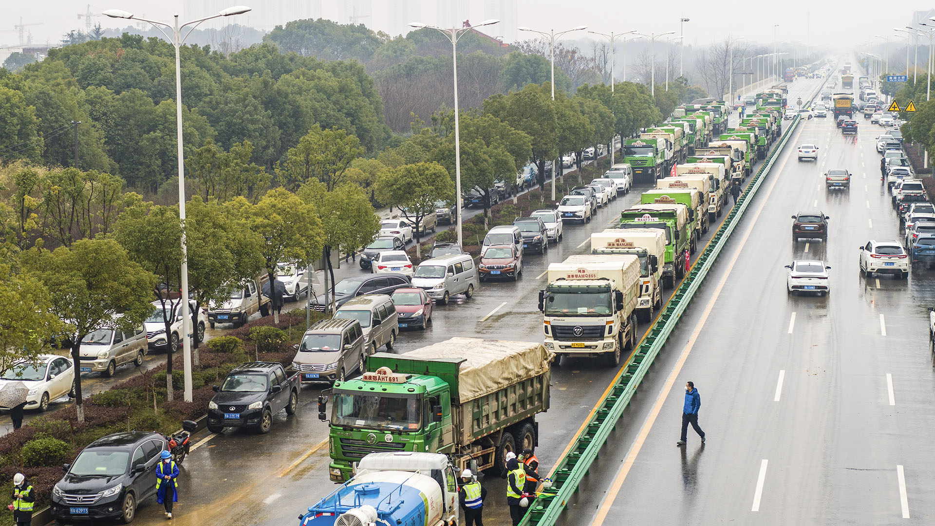 Los camiones hacen cola para ingresar al sitio de construcción del hospital (Foto por STR / AFP)