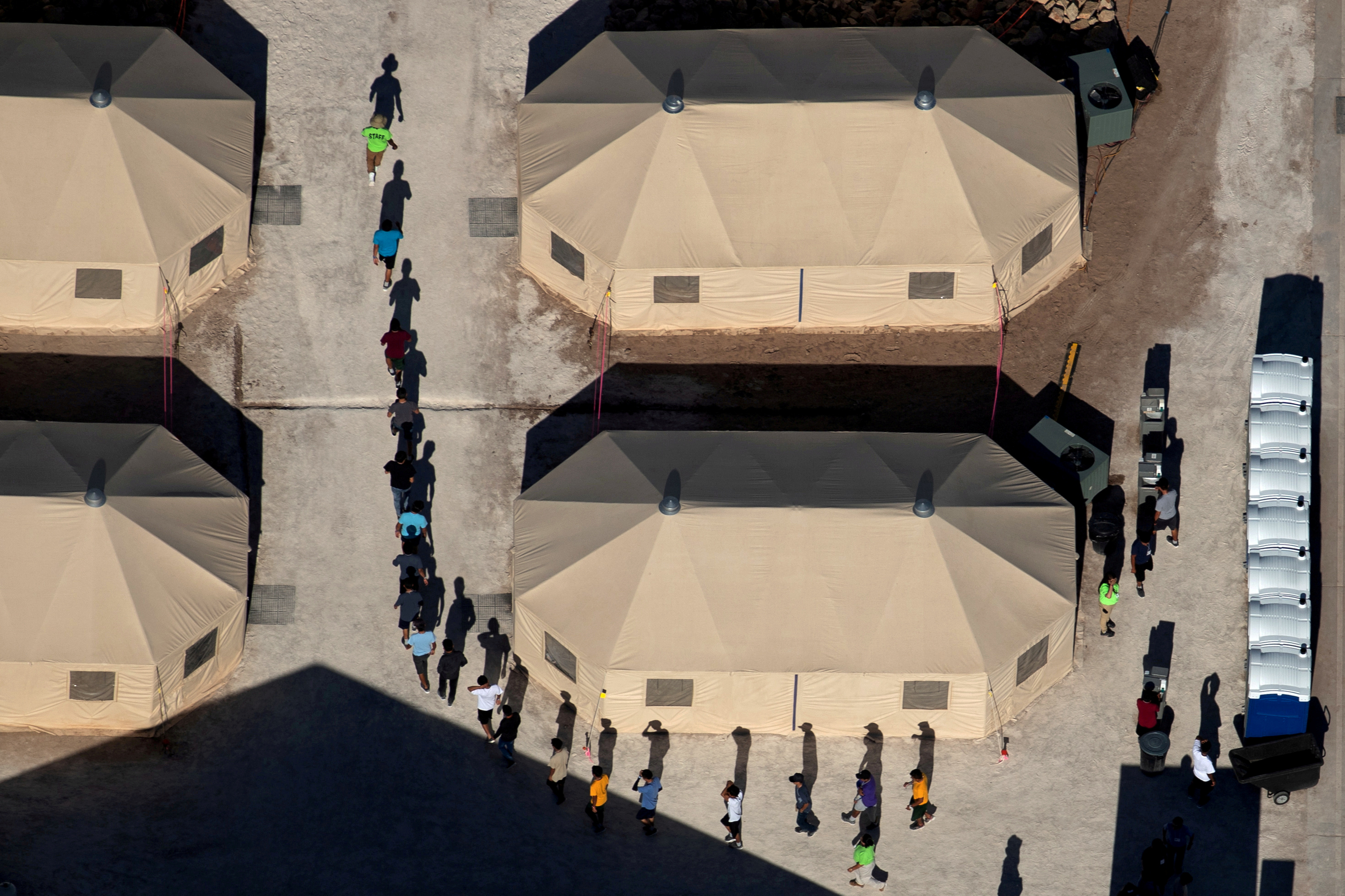 Niños inmigrantes son guiados en fila entre tiendas de campaña en un centro de detención cerca de la frontera con México en Tornillo, Texas, el 18 de junio de 2018 (REUTERS/Mike Blake)