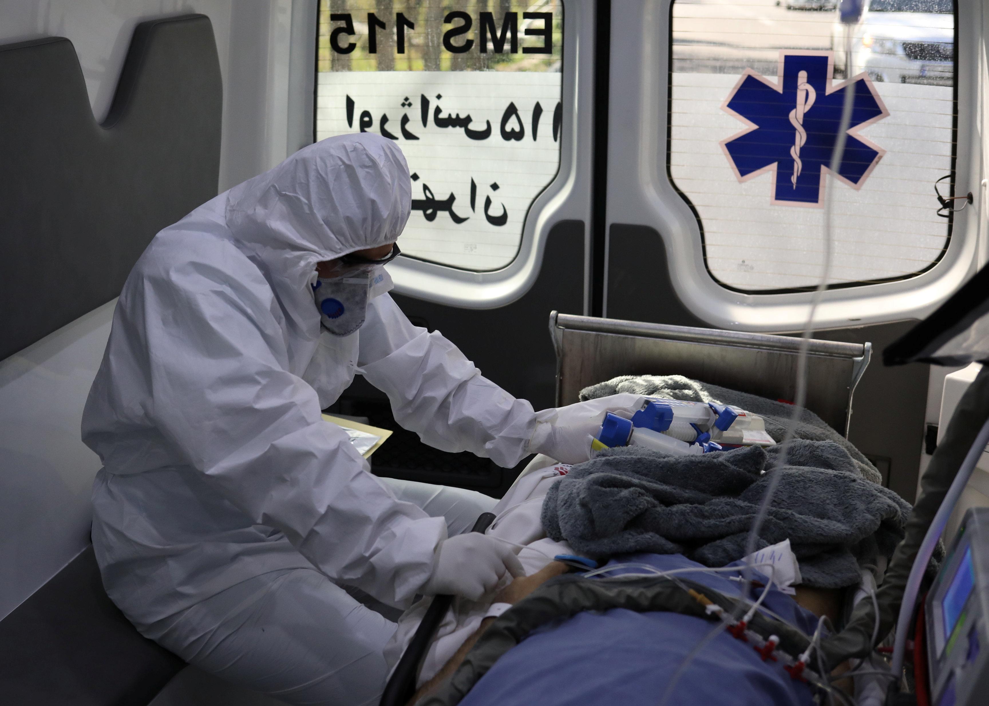Un miembro del personal médico de emergencia con traje protector se sienta en una ambulancia mientras traslada a un paciente con coronavirus al Hospital Masih Daneshvari, en Teherán, Irán (REUTERS)