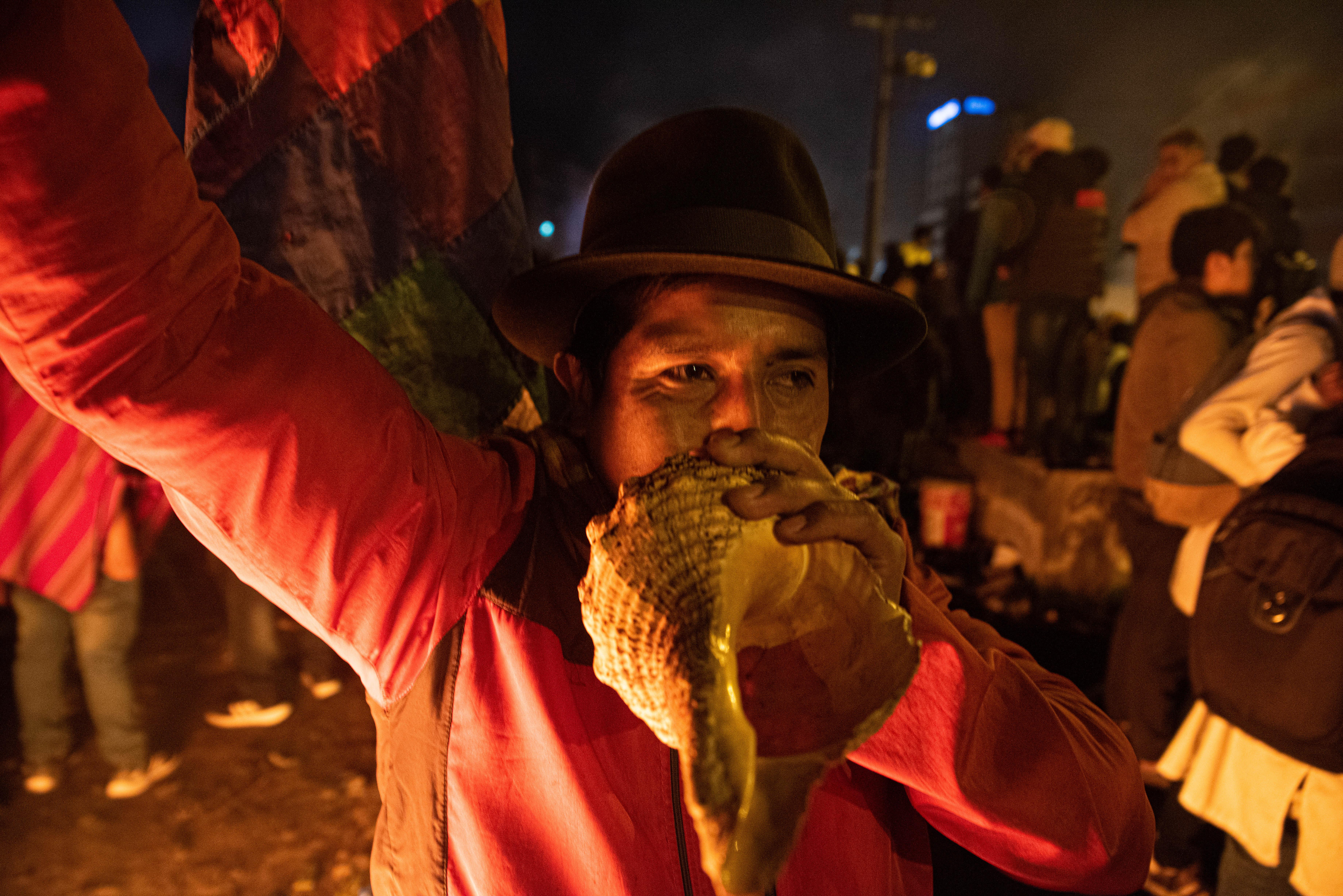 Un hombre toca una caracola para simbolizar el fin de la batalla campal que se libro entre la policía y miles de manifestantes en las calles de Quito y el resto del país
