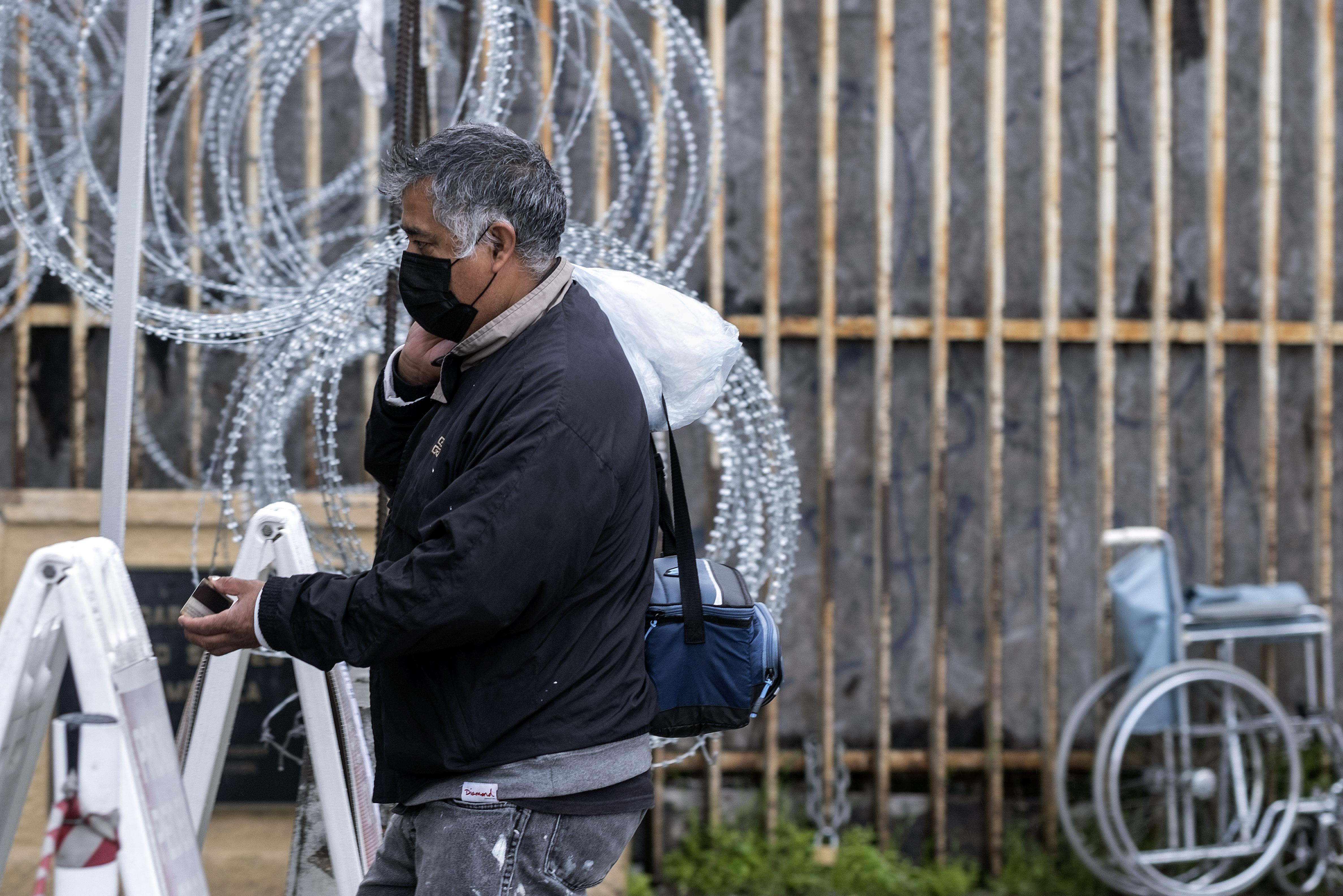 Un hombre con una máscara protectora muestra su documento a los agentes de Aduanas y Protección Fronteriza en el puerto de entrada de San Ysidro en la frontera entre Estados Unidos y México en Tijuana, estado de Baja California, México, el 19 de marzo de 2020.
