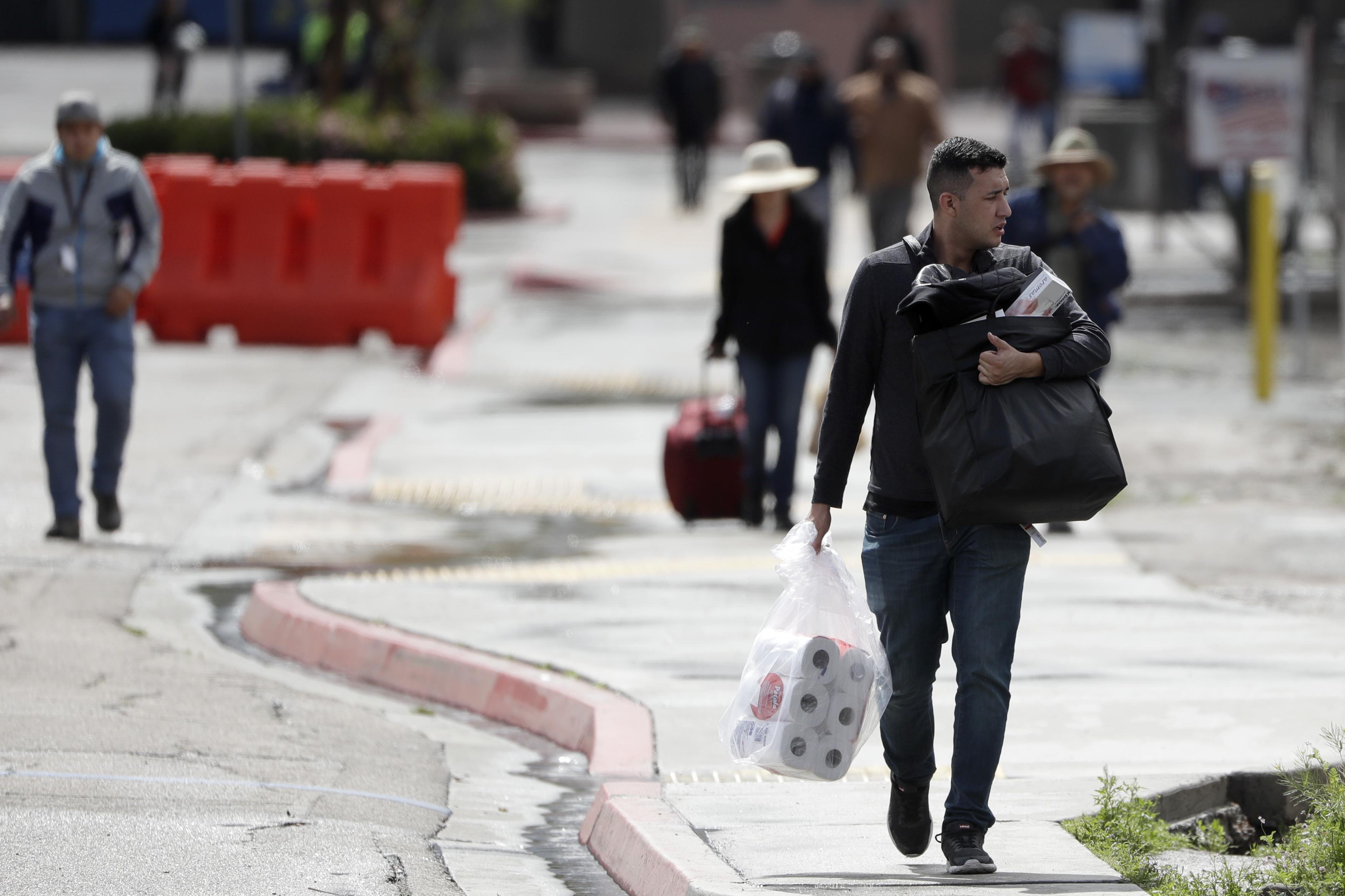 Un hombre lleva papel higiénico después de cruzar la frontera desde Tijuana, México, a San Diego, el miércoles 18 de marzo de 2020, en San Diego.