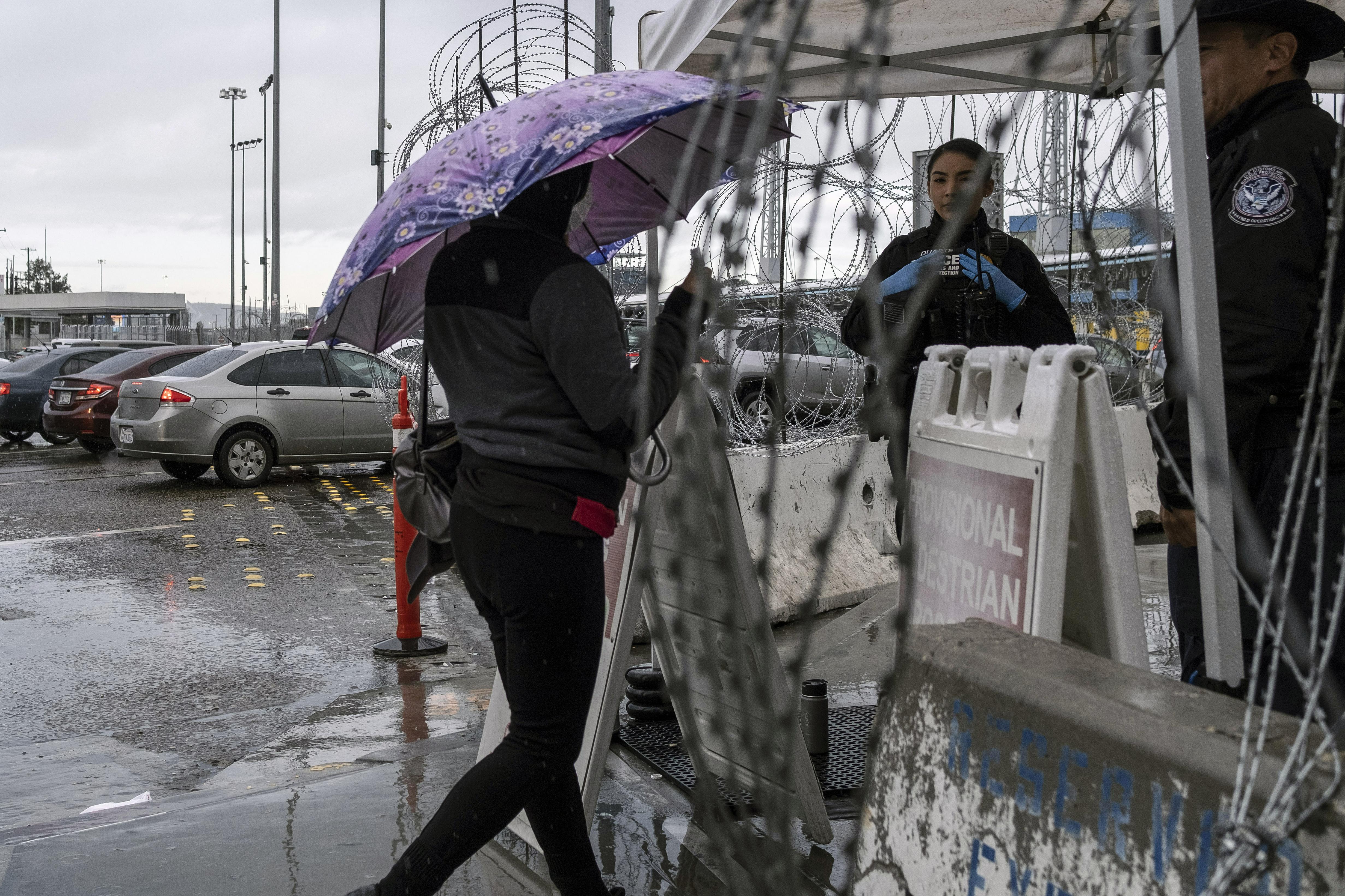 Una mujer que llevaba una máscara protectora muestra su documento a los agentes de Aduanas y Protección Fronteriza en el puerto de entrada de San Ysidro en la frontera entre Estados Unidos y México en Tijuana, estado de Baja California, México, el 19 de marzo de 2020.