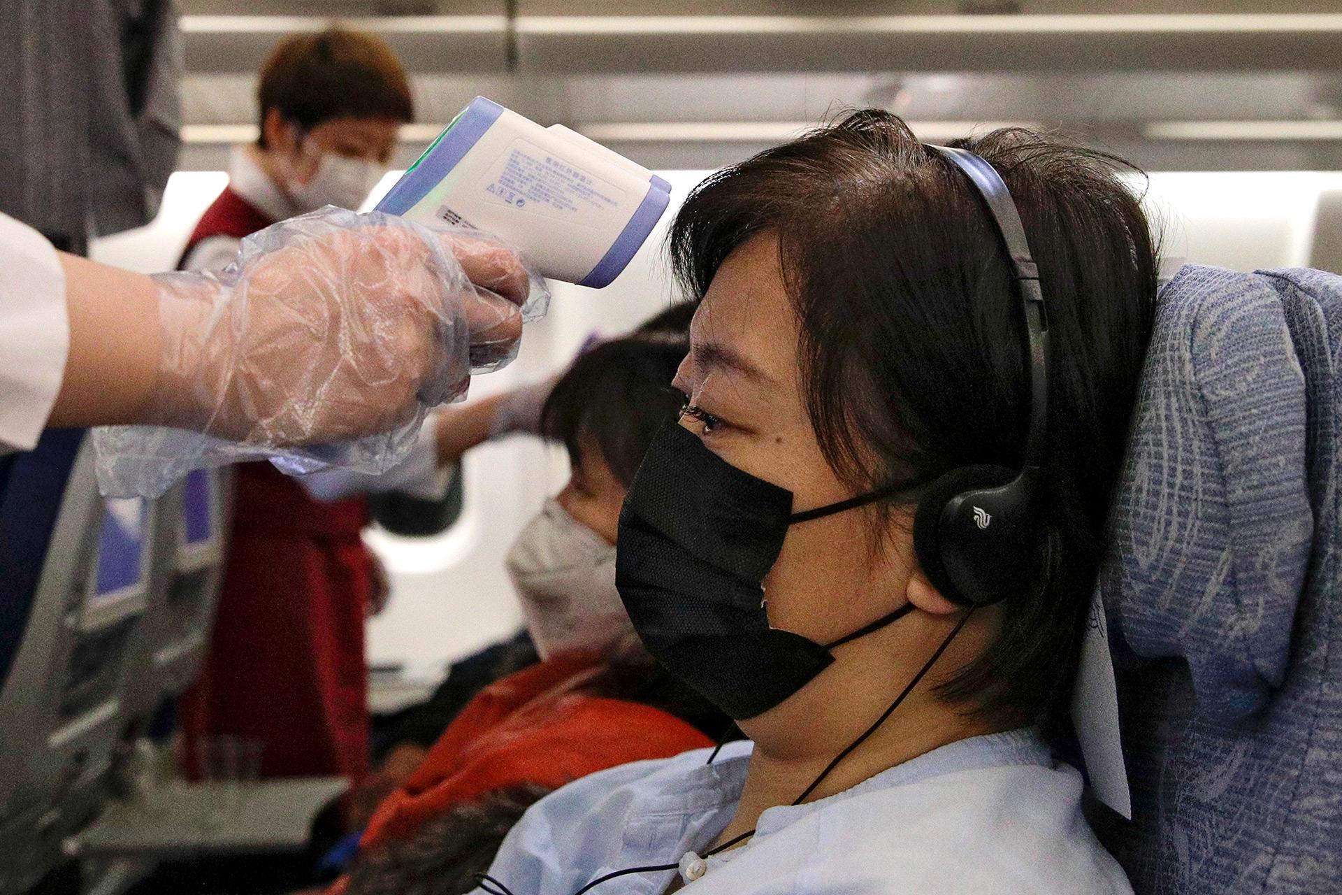 Las azafatas toman la temperatura de los pasajeros como medida preventiva para el coronavirus en un vuelo de Air China desde Melbourne a Beijing antes de aterrizar en el Aeropuerto Internacional Capital de Beijing en China, el martes 4 de febrero de 2020 (AP / Andy Wong)