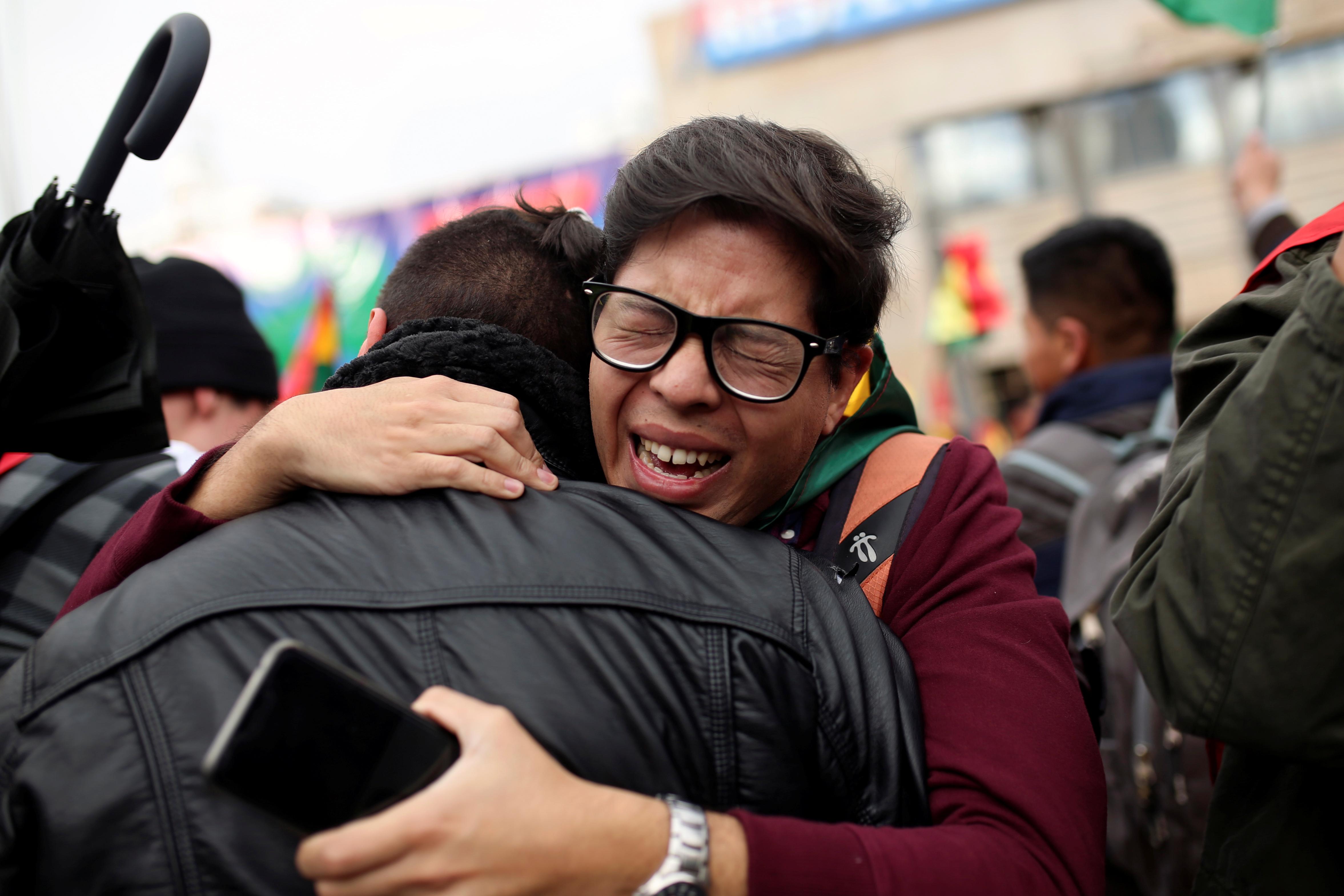 Una pareja se abraza tras conocer la renuncia de Morales