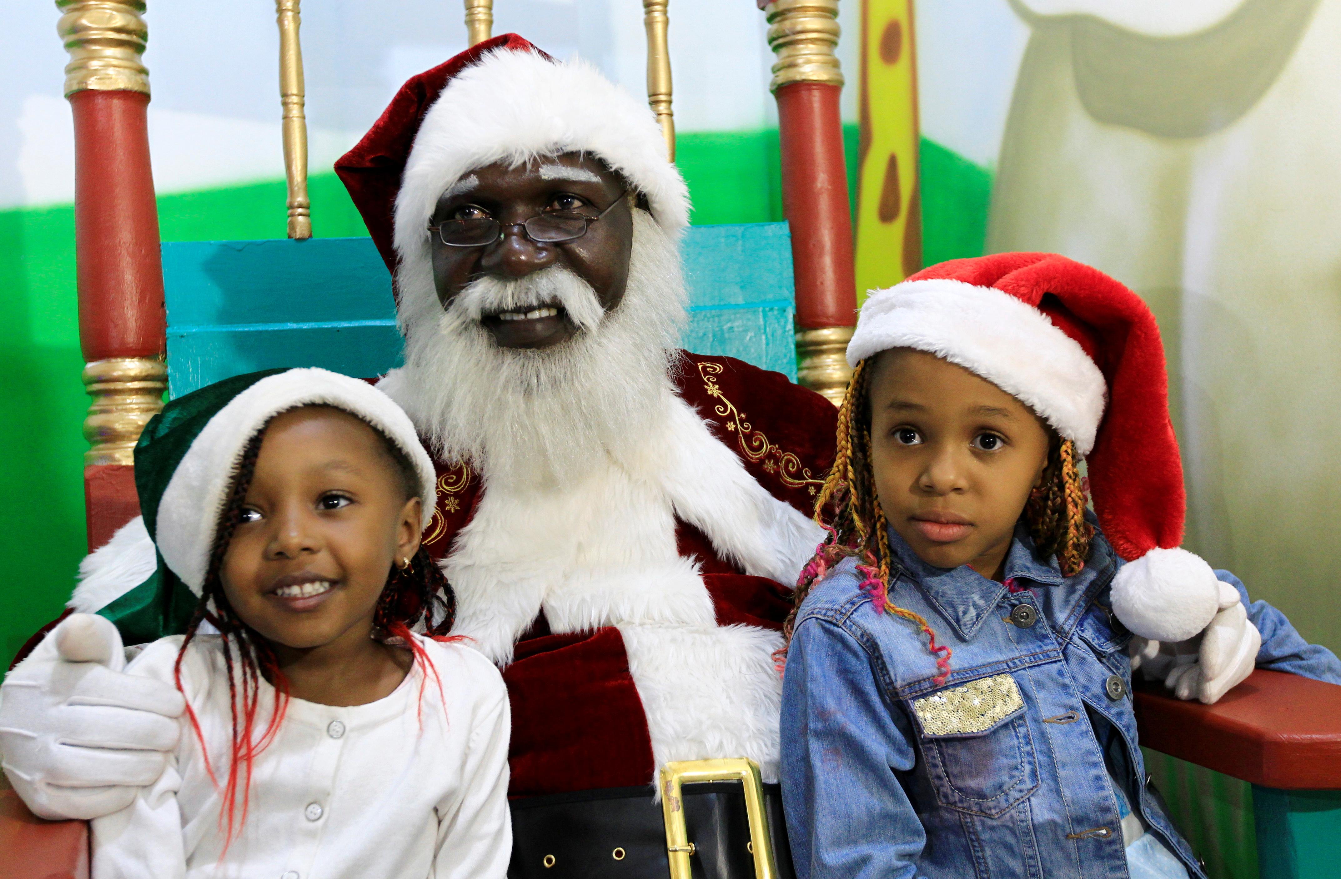 El Papá Noel africano Zedekiah Miyare, de 56 años, posa para una fotografía con niños en un centro comercial antes de Navidad en Nairobi, Kenia, 21 de diciembre de 2019 (Reuters/ Njeri Mwangi)