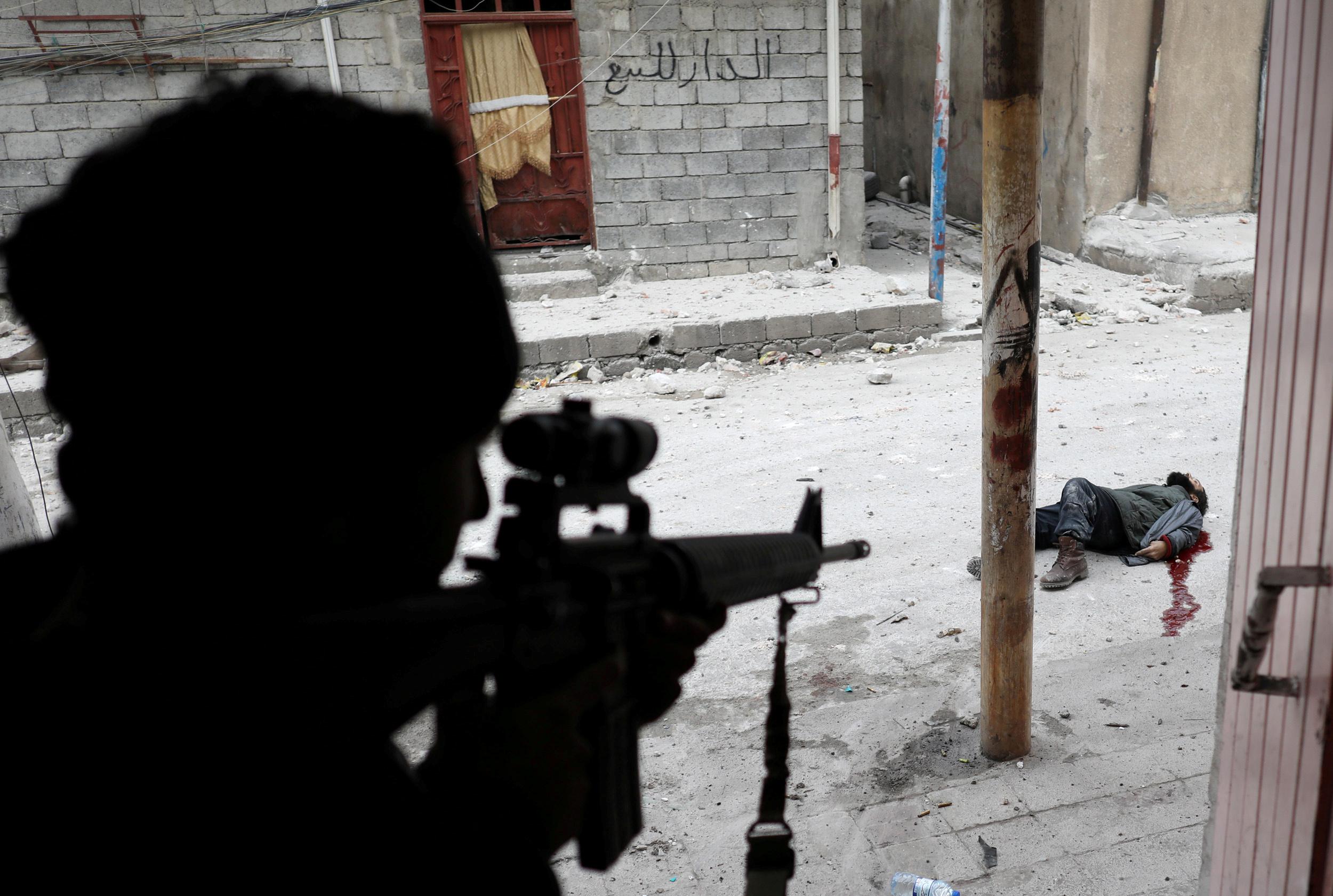 Un soldado de las fuerzas especiales iraquíes dispara a un terrorista suicida del Estado Islámico, en Mosul, Irak, el 3 de marzo de 2017 (REUTERS/Goran Tomasevic)