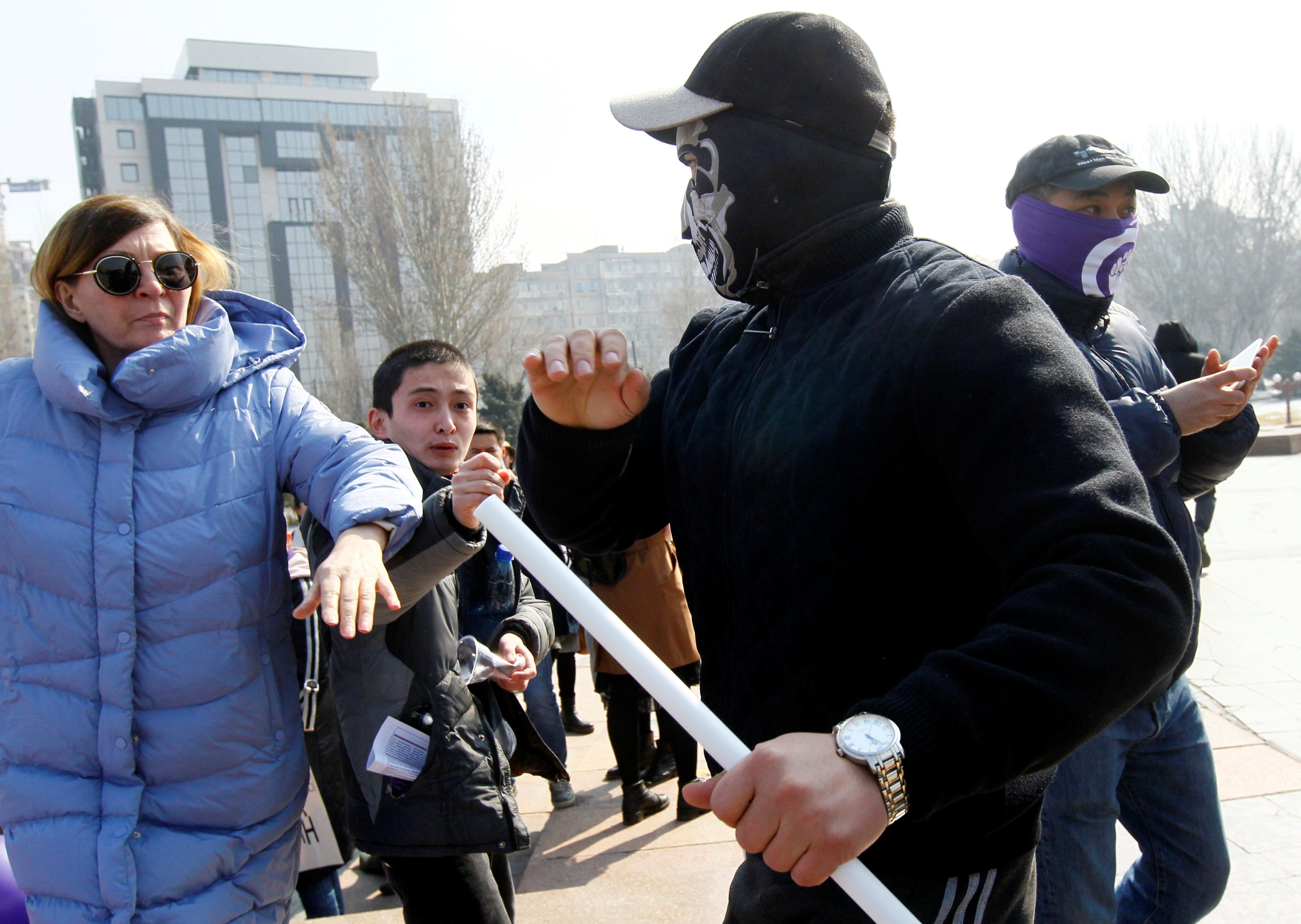 Un hombre con una máscara ataca a una mujer durante una marcha en Bishkek, Kirguistán (REUTERS/Vladimir Pirogov)