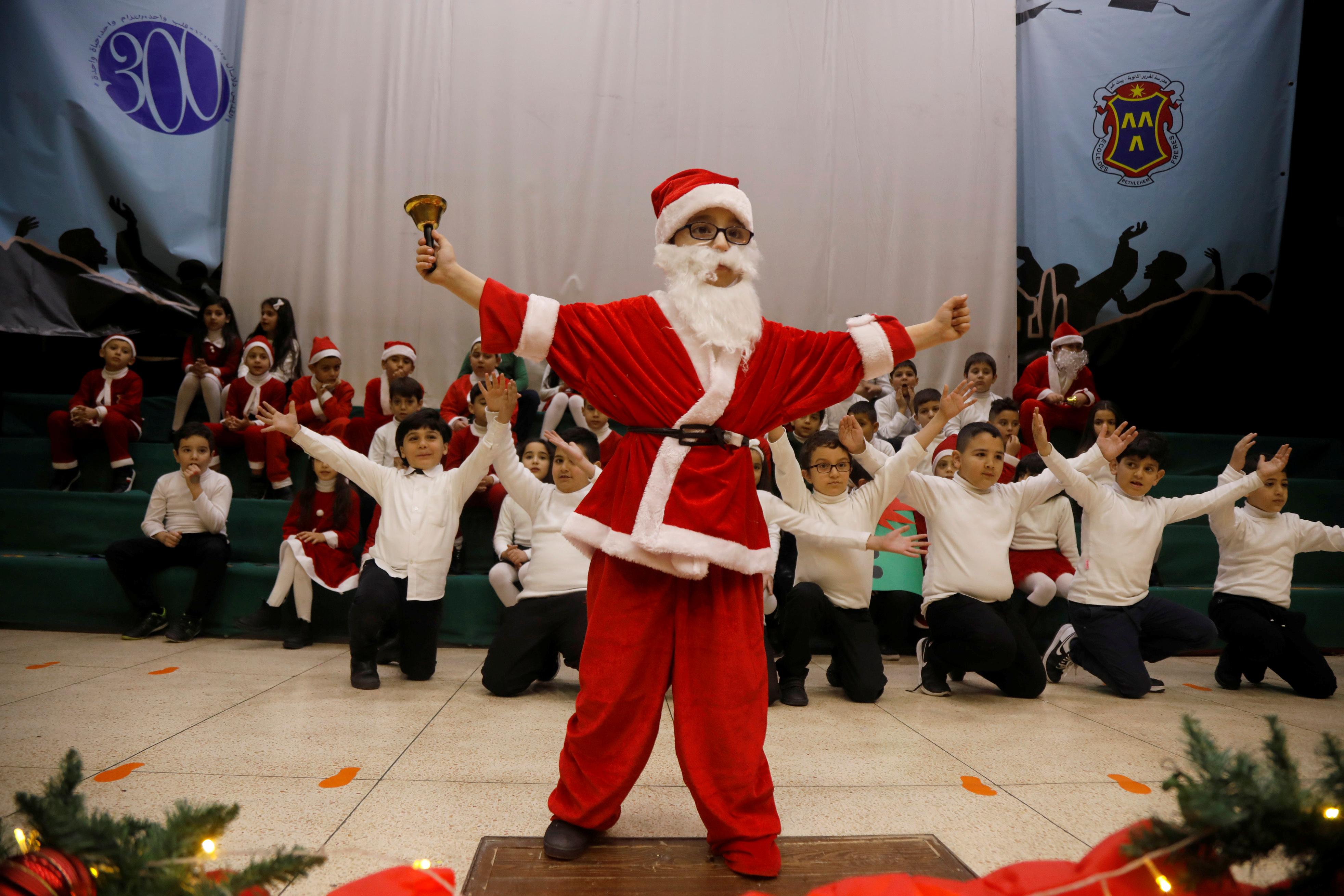 Un niño palestino vestido como Santa Claus se presenta en un espectáculo navideño en la escuela College Des Freres en Belén, en la Cisjordania ocupada por Israel el 17 de diciembre de 2019 (Fotografía tomada el 17 de diciembre de 2019 (Reuters/ Raneen Sawafta)