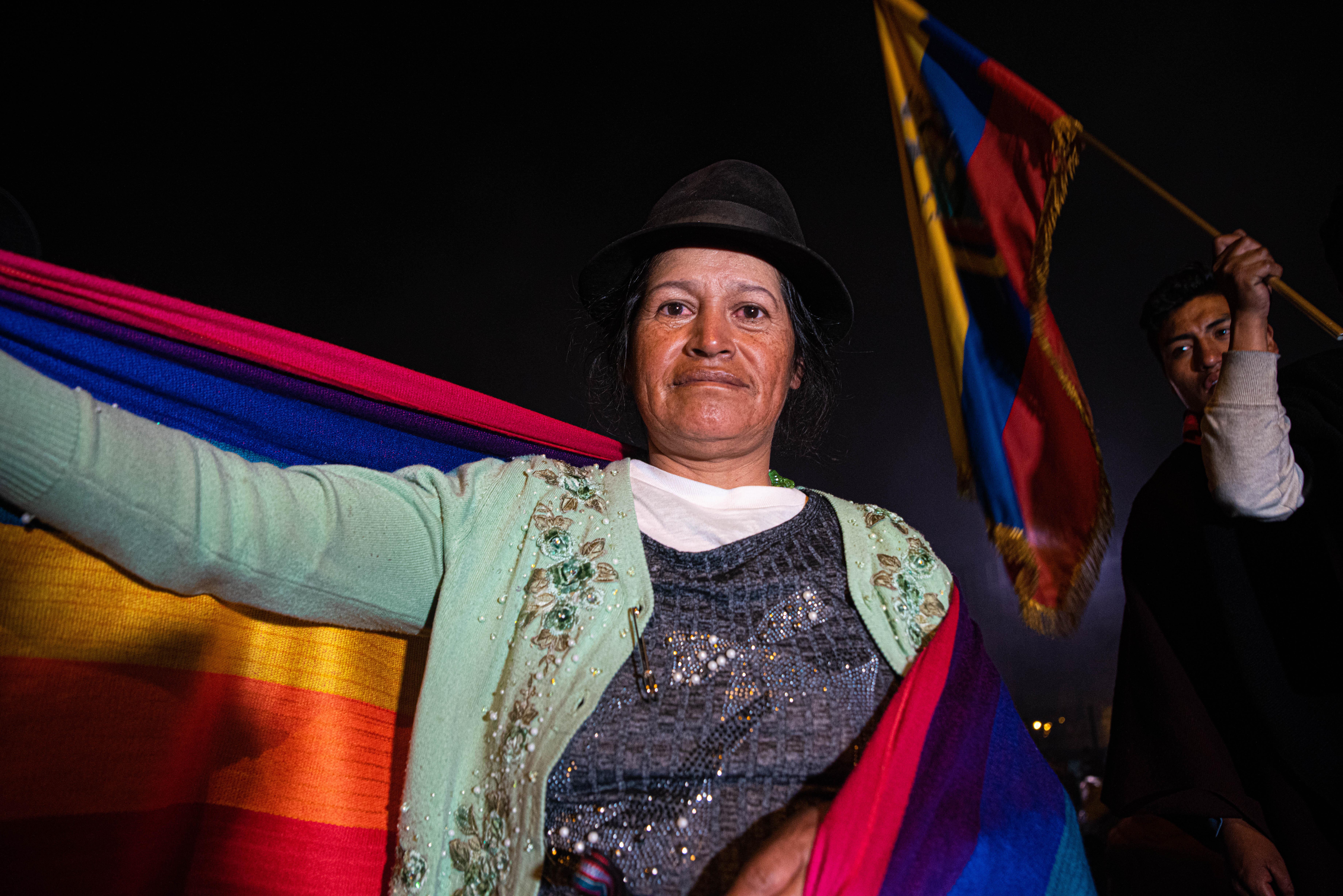 Una mujer indígena celebra con la bandera de Ecuador en sus hombros