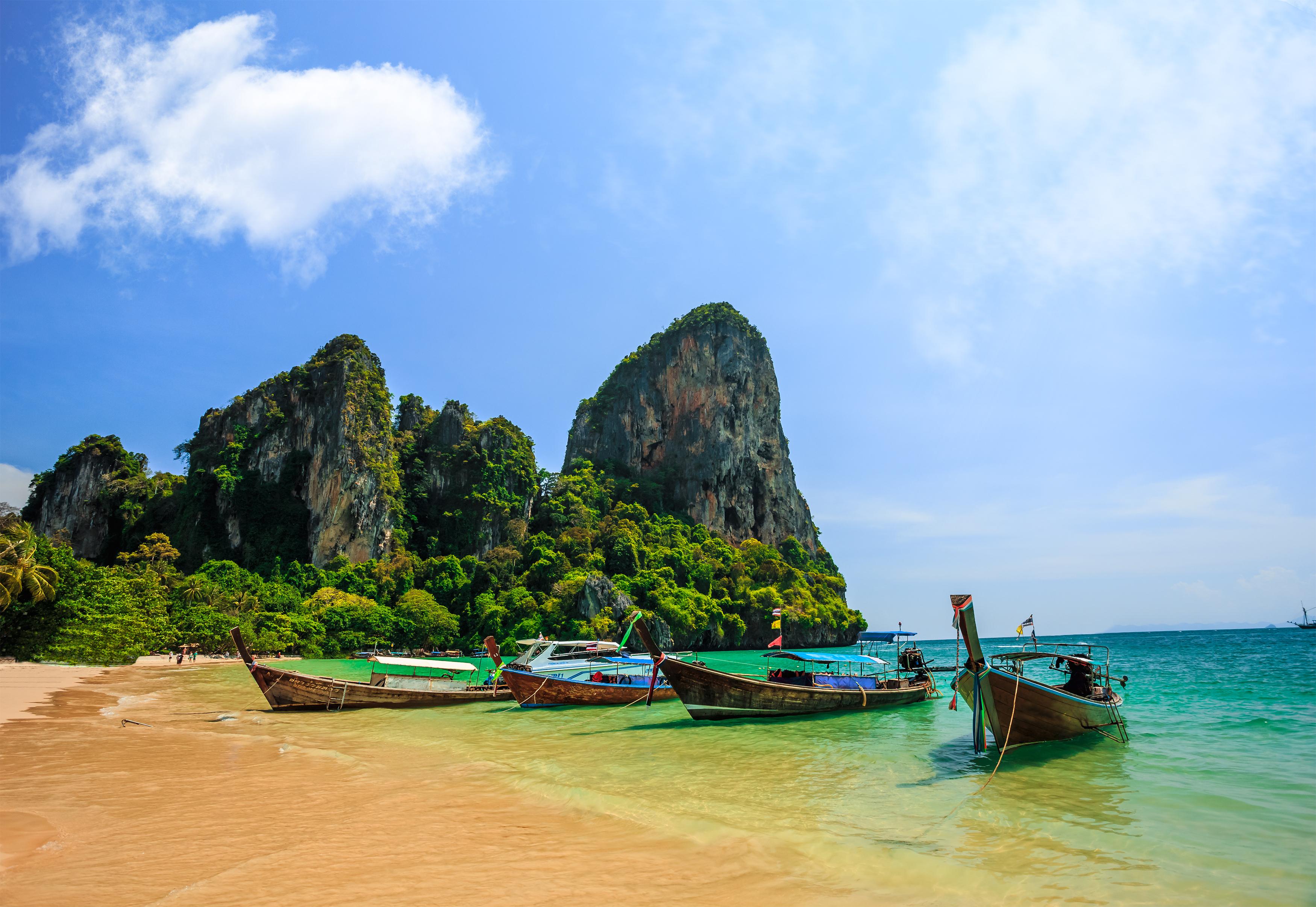 Los acantilados adornados con musgo y hierba se elevan de fondo mientras el mar choca contra la orilla, todo mientras los barcos de pesca flotan en el mar. Estar en la playa de Ao Nang es una experiencia tailandesa única
