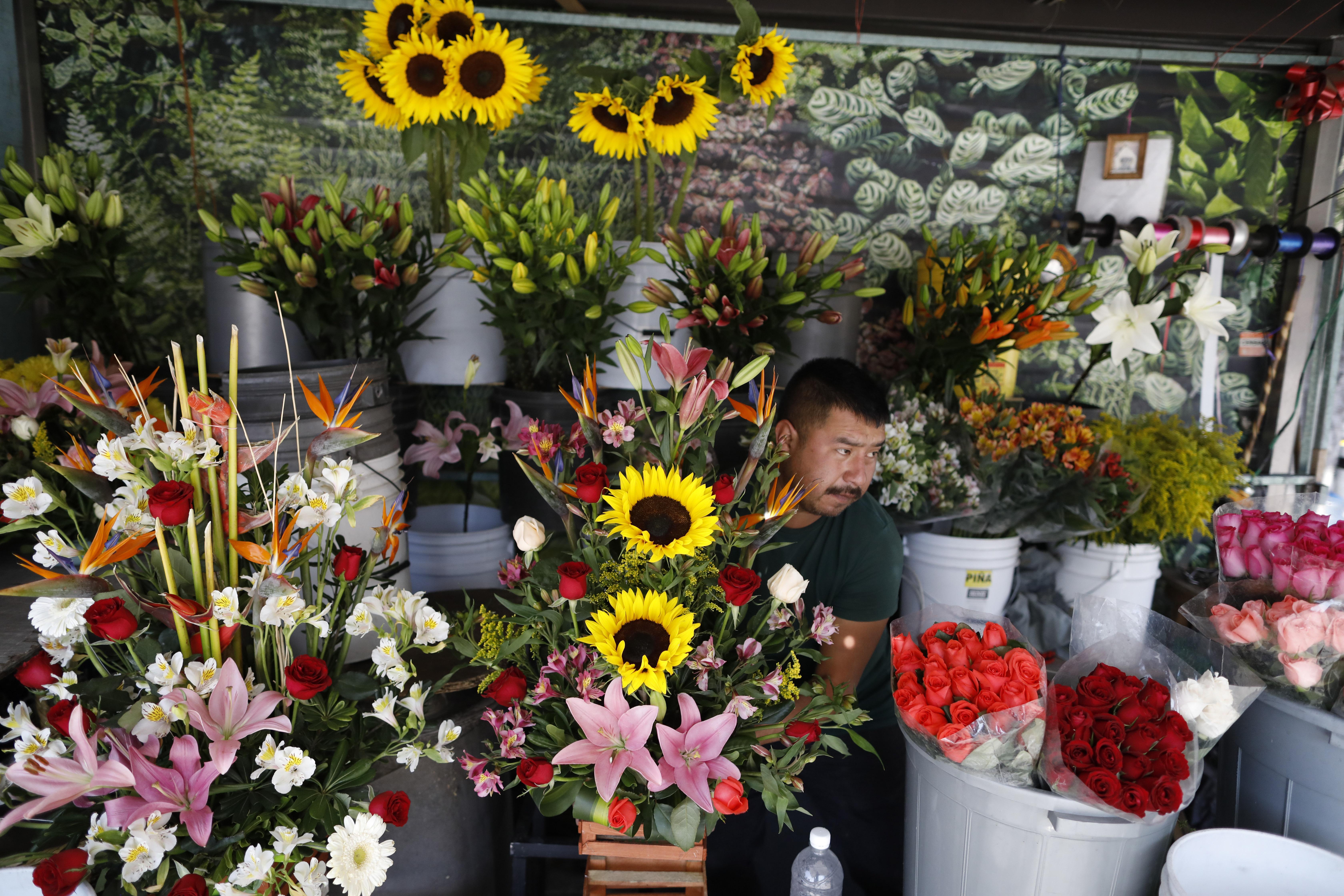Un vendedor de flores que prefirió no dar su nombre organiza sus flores para exhibirlas cuando abra su puesto callejero en la Ciudad de México, el miércoles 25 de marzo de 2020.