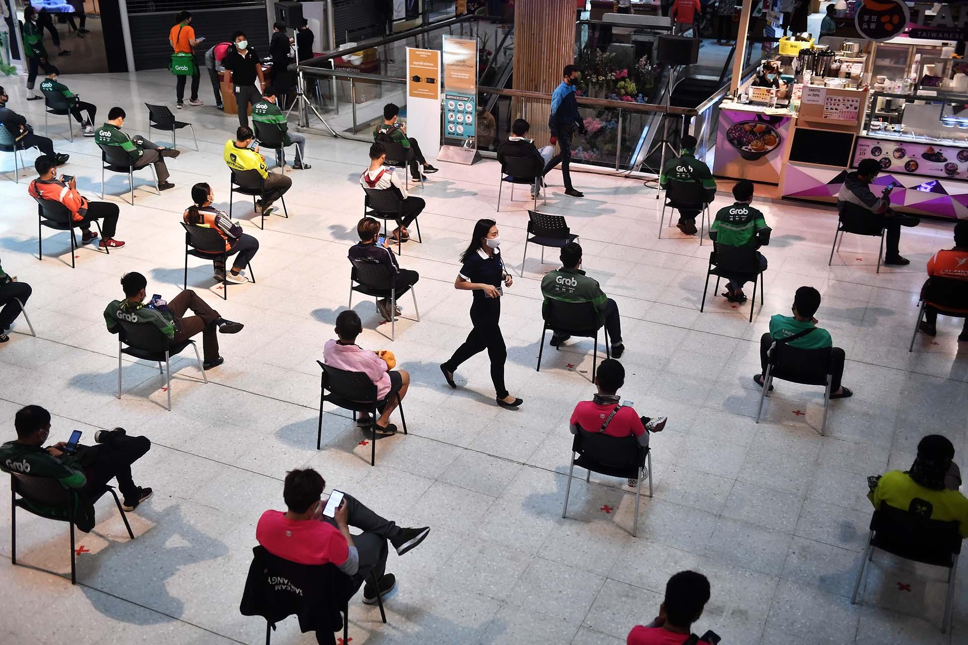 Repartidores de comida y clientes esperan pos sus pedidos en un centro comercial de Pinklao en Bangkok