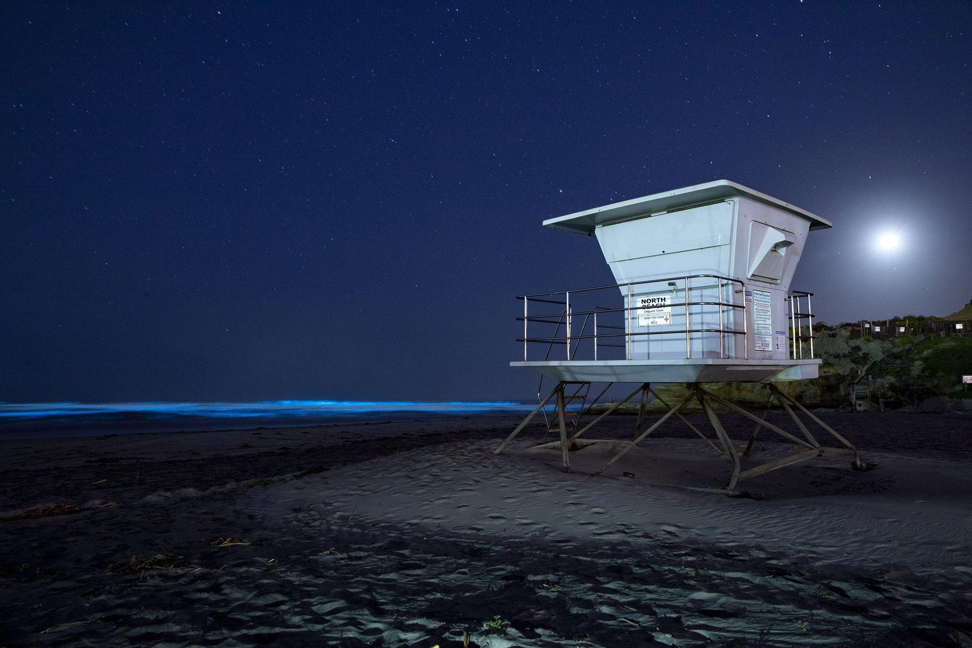 Las olas brillan con la bioluminiscencia azul de una floración de algas en las aguas del océano mientras una torre de salvavidas se sienta en una playa aún cerrada en Del Mar, California, el lunes 27 de abril de 2020 (AP Photo / Gregory Toro)