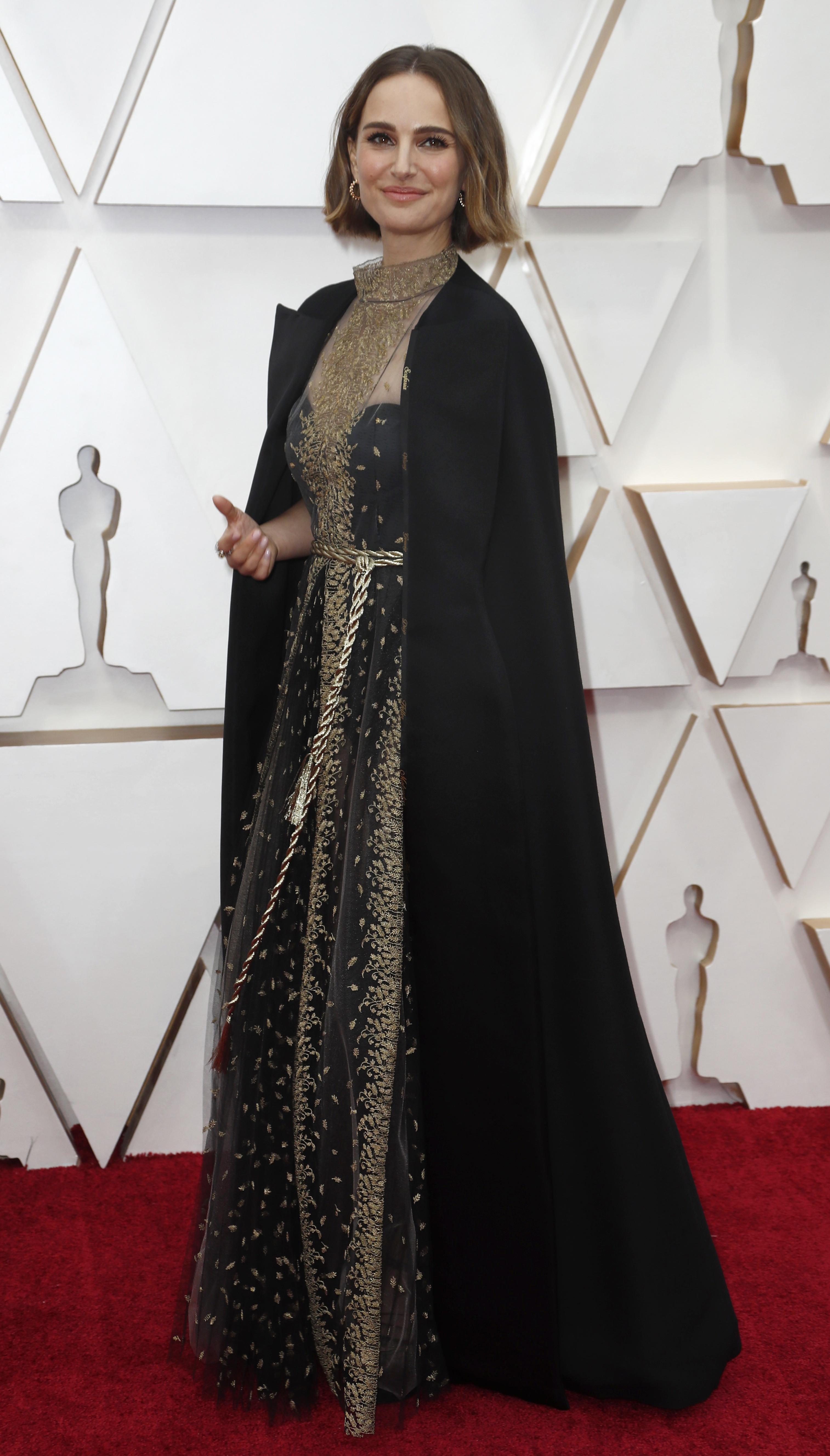 Natalie Portman apostó a un vestido negro bordado de cuello cerrado con una gran capa negra que tenia detalles de grabado con los nombres de las directoras mujeres que no estuvieron nominadas en los premios. Completó su look con pequeñas argollas joya y anillos