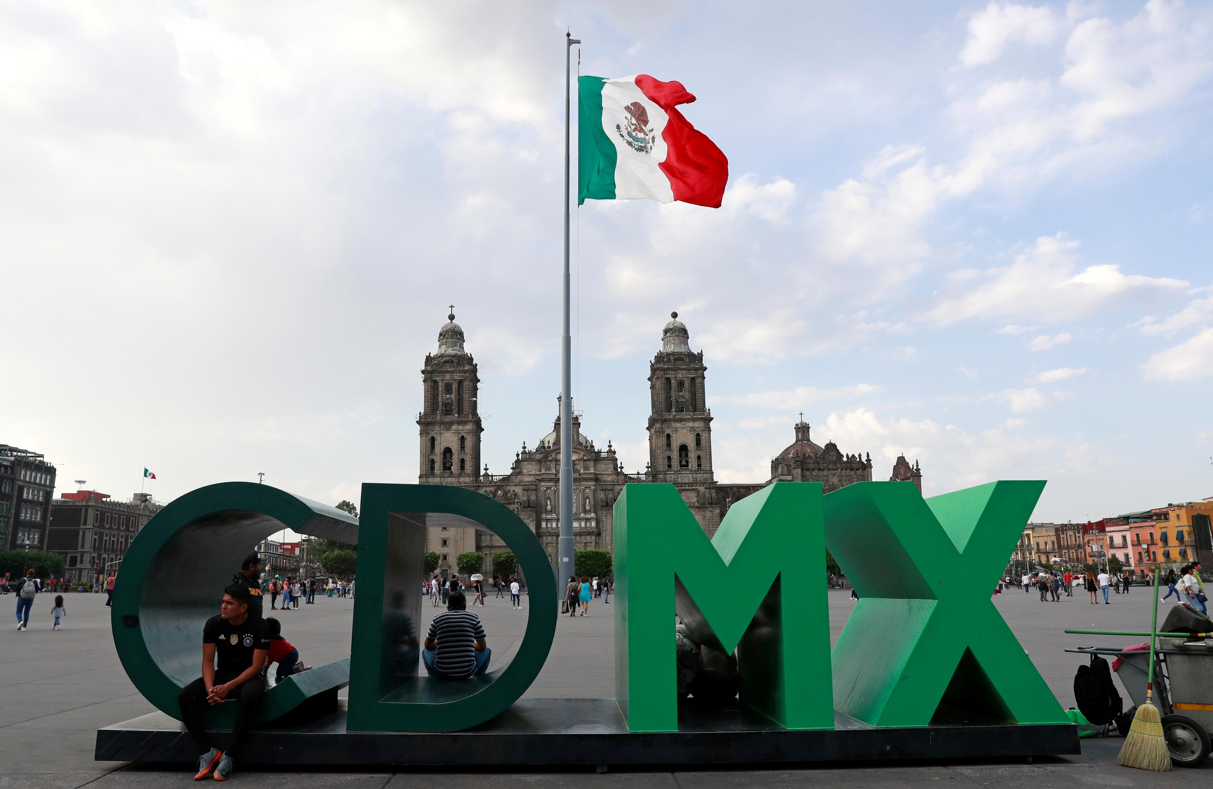 Se ve a personas cerca de la bandera nacional en la Plaza Zócalo cuando las autoridades de salud de México comenzaron a implementar medidas más estrictas para contener la propagación de la enfermedad por coronavirus (COVID-19), en la Ciudad de México, México, 22 de marzo de 2020.
