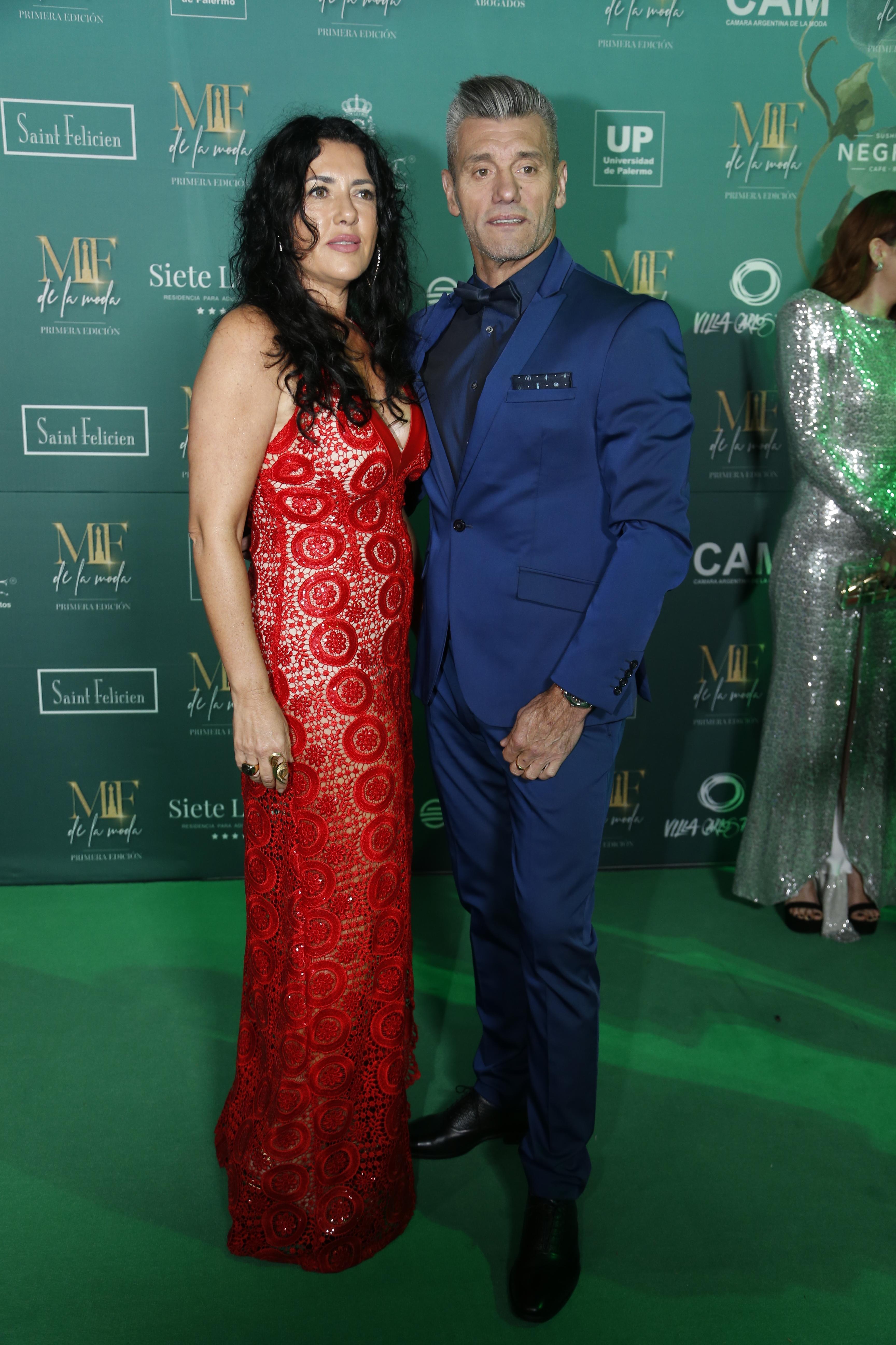 Sergio Goycochea con un smoking azul y su mujer con un vestido rojo en la green carpet