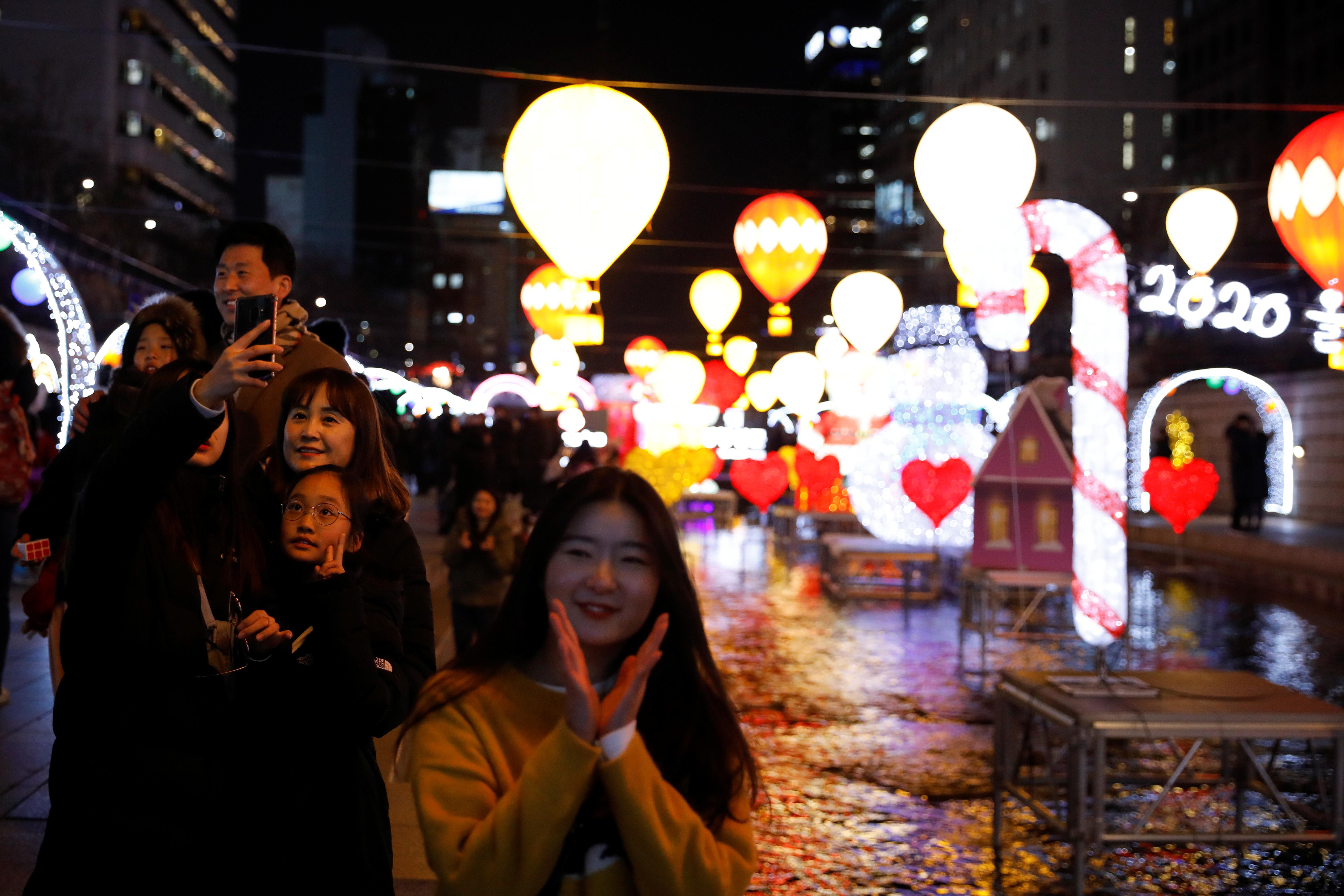 Coreanos se sacan selfies durante la celebración del año nuevo en las calles de Seúl