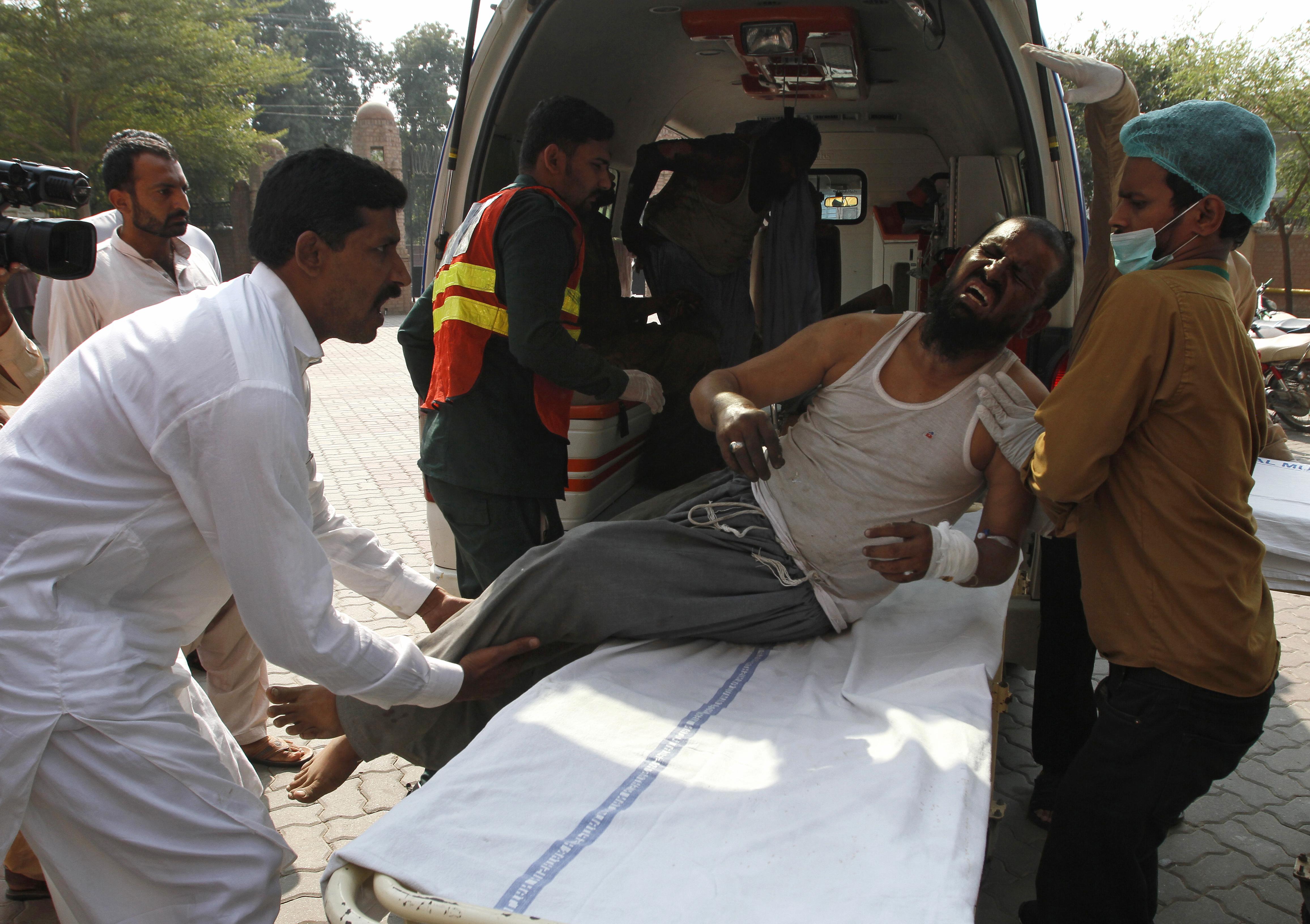 El personal del hospital trasladó a un hombre que resultó herido en el incendio de un tren a un hospital en Multan, Pakistán, (AP Photo / Asim Tanveer)