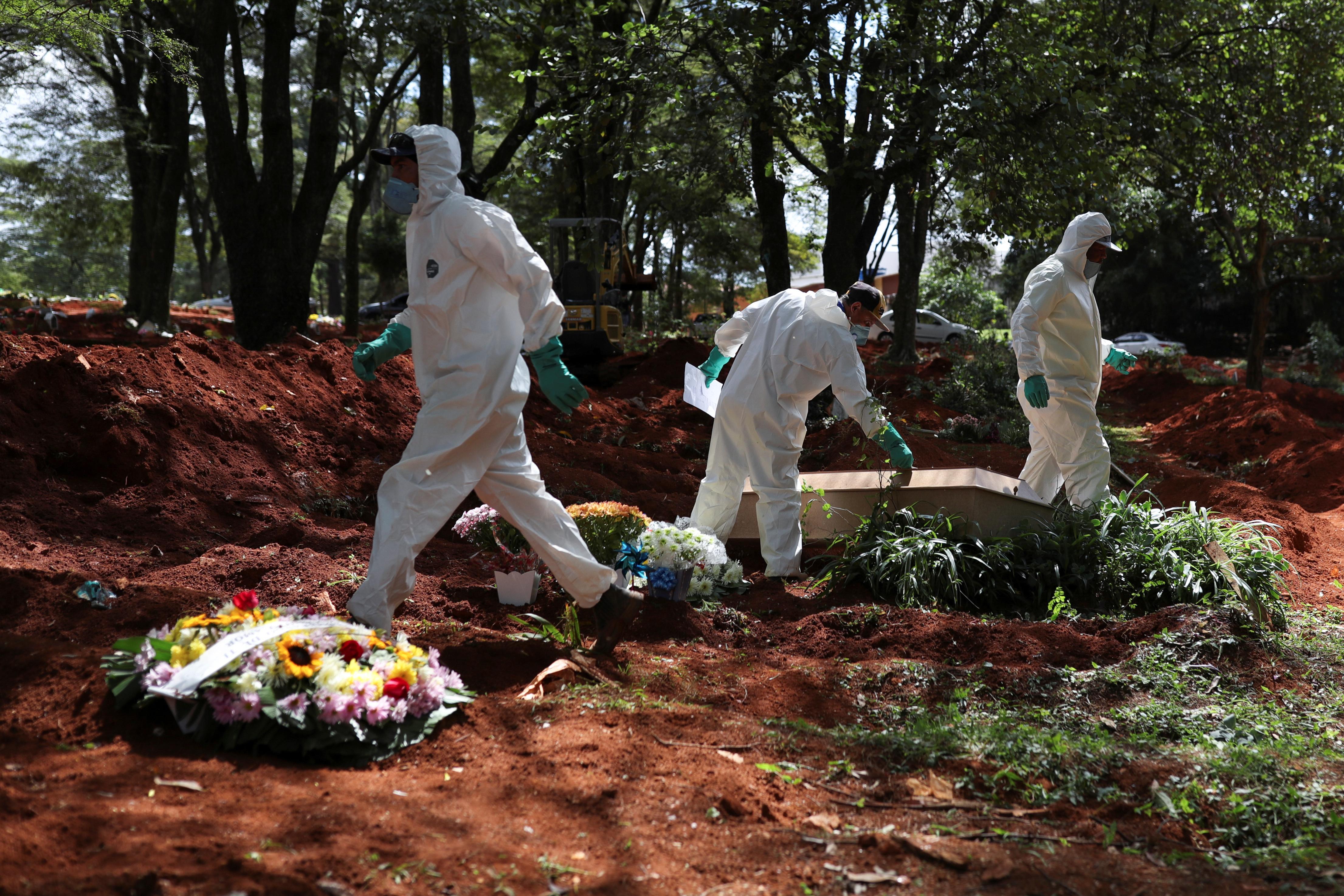 Trabajadores del cementerio más grande de Brasil, Vila Formosa, en San Pablo, trabajan contra reloj para alcanzar a enterrar a los muertos que llegan como consecuencia del brote de coronavirus (Reuters)