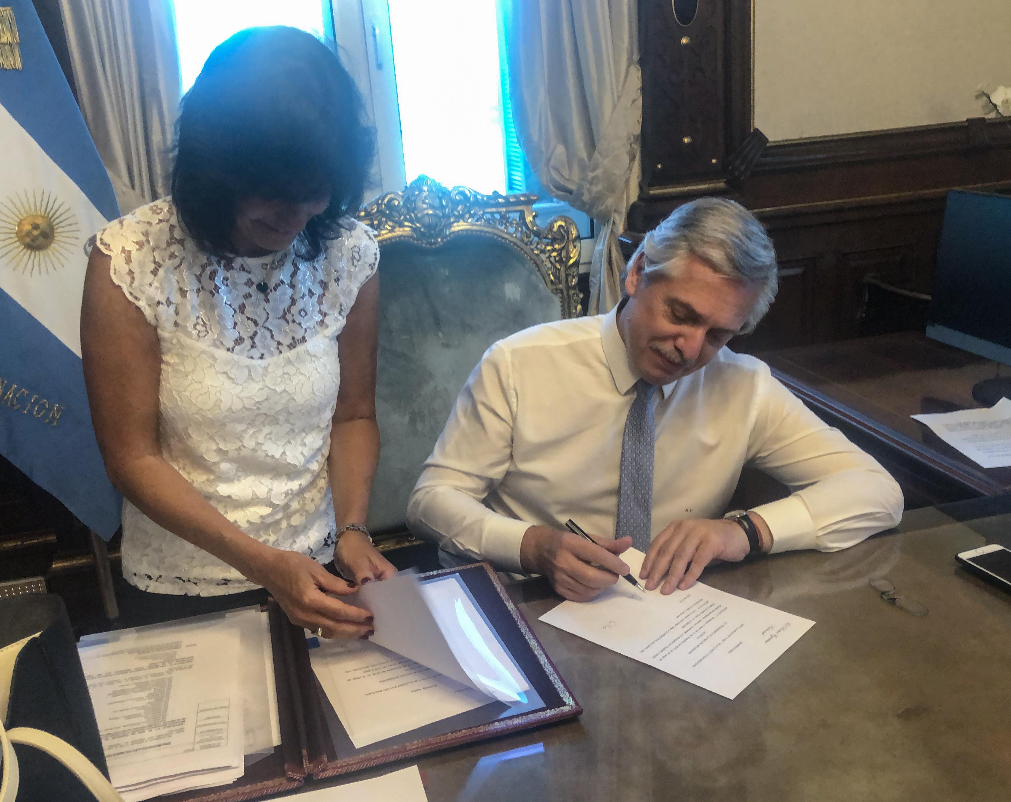 El presidente Alberto Fernández firmando las designaciones de sus ministros antes de la jura formal, junto a su secretaria Legal y Técnico Vilma Ibarra