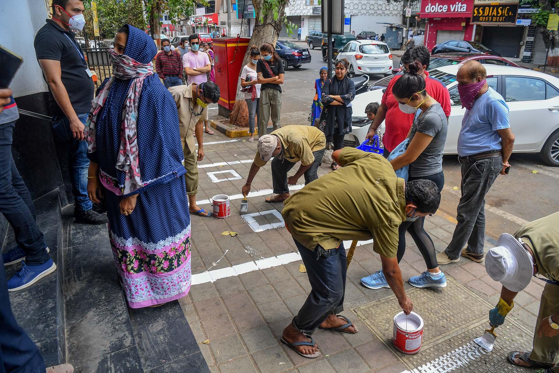 Trabajadores municipales pintan lineas en el suelo para mantener la distancia social frente a una tienda en Mumbai, India.