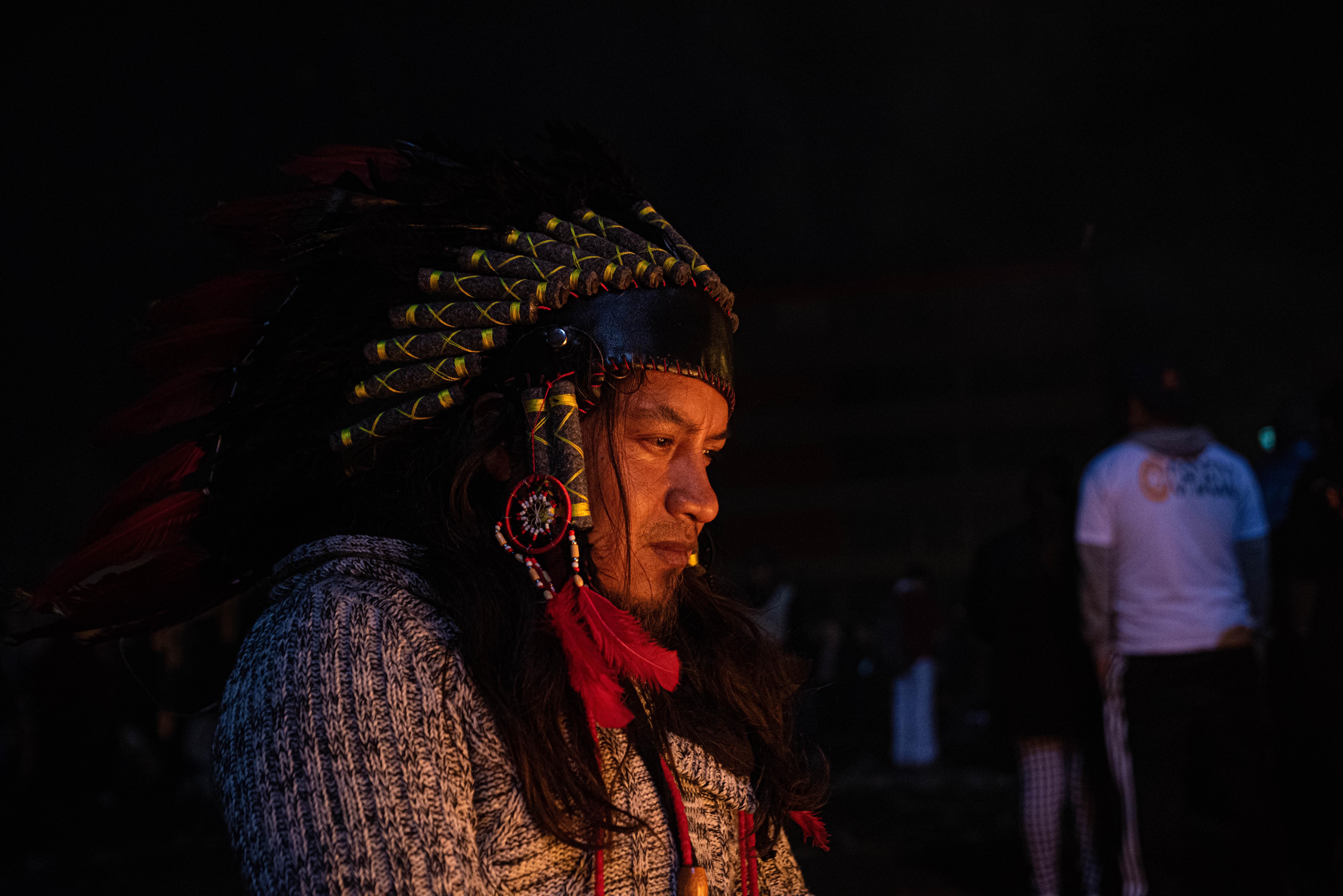 Un hombre con vestimenta tradicional aborigen en medio de los festejos en las calles de Quito.