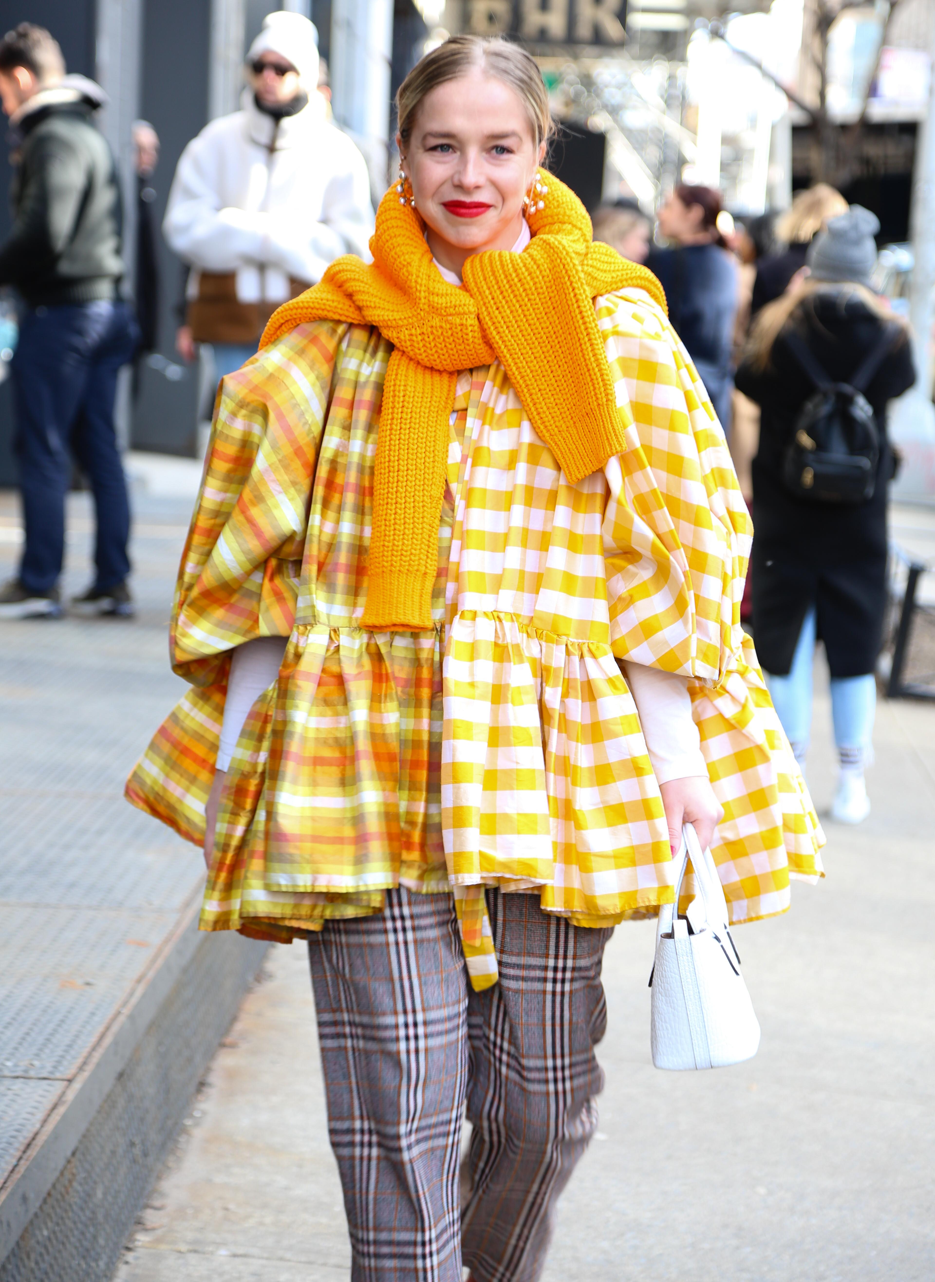 Cuadros alert. Blusa oversized en amarillo y blanco cuadrillé, combinada con pantalón príncipe de gales. Completó su outfit para el NYFW con una gran bufanda tejida
