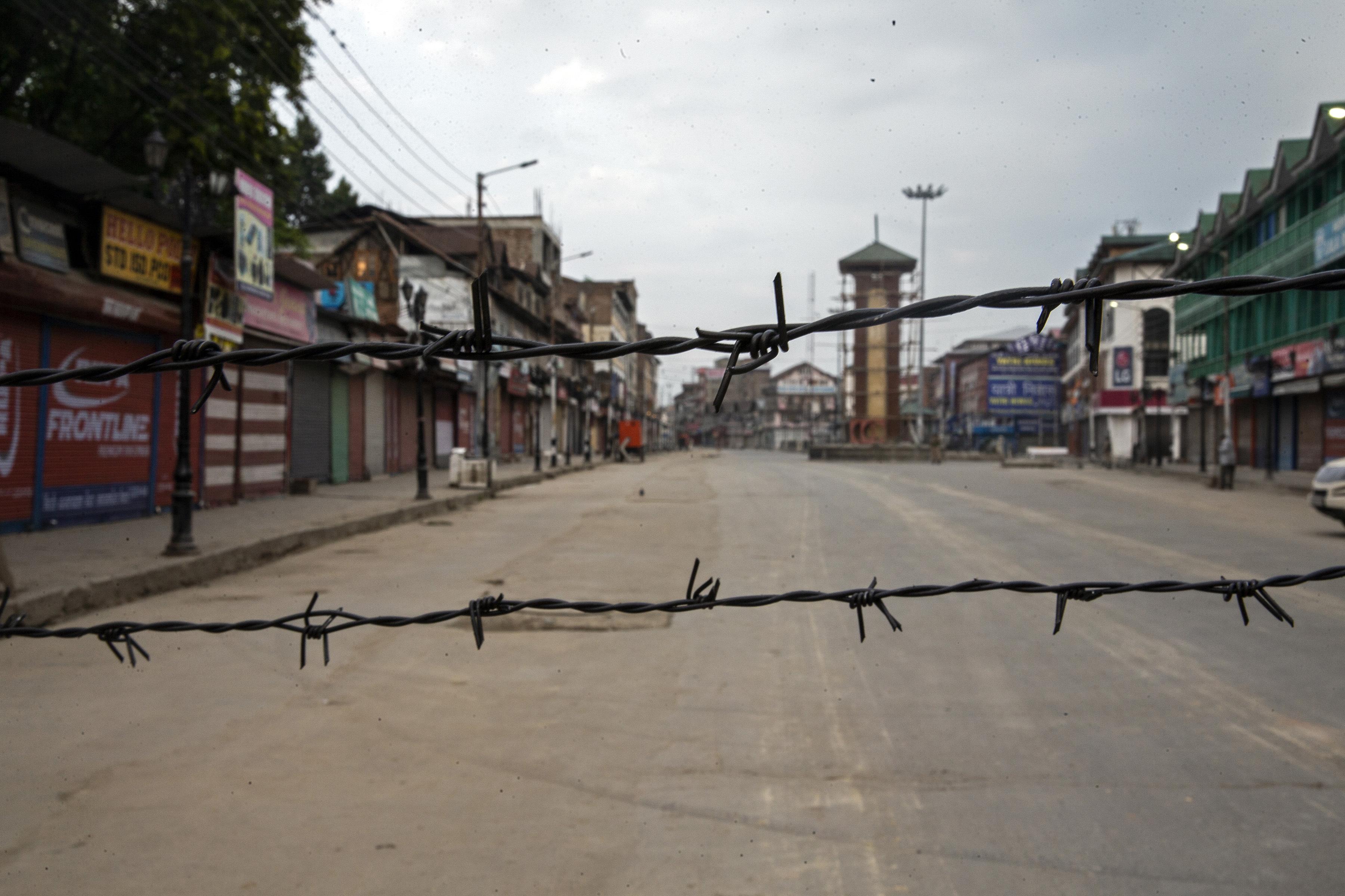 Una calle desierta se ve a través del alambre de púas creado como un bloqueo durante el toque de queda en Srinagar, Cachemira controlada por la India, el 6 de agosto de 2019. (Foto AP / Dar Yasin)