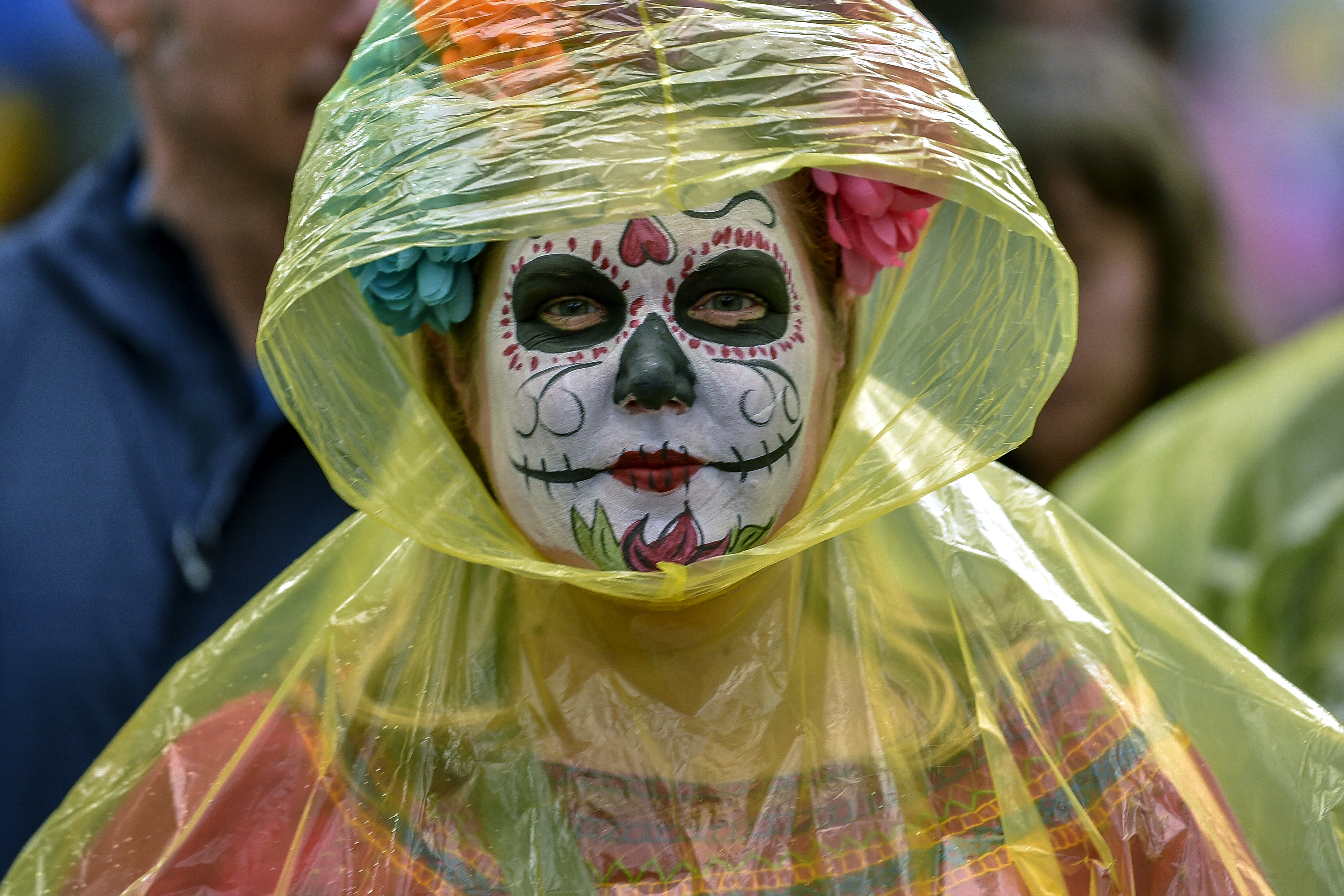 Una mujer ser proteje de la lluvia con una delgada capa de plástico (Foto: Pedro Pardo/AFP)