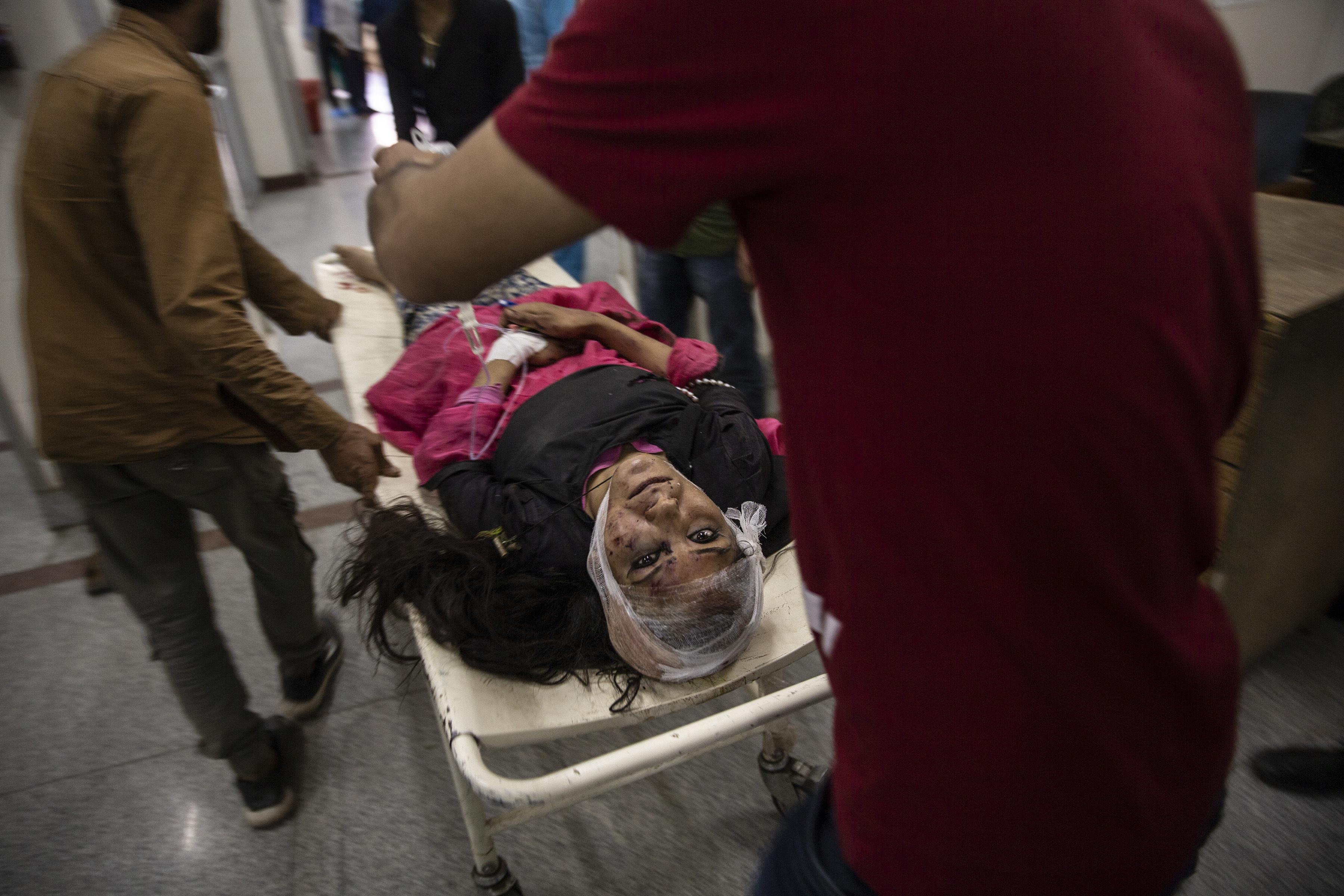 Una mujer herida es llevada en una camilla para recibir tratamiento después de ser herida en un accidente de autobús, en un hospital local en Srinagar, Cachemira controlada por la India, el 27 de junio de 2019. Un minibús que llevaba estudiantes a un picnic cayó en una garganta a lo largo de una carretera del Himalaya. en Cachemira (Foto AP / Dar Yasin)