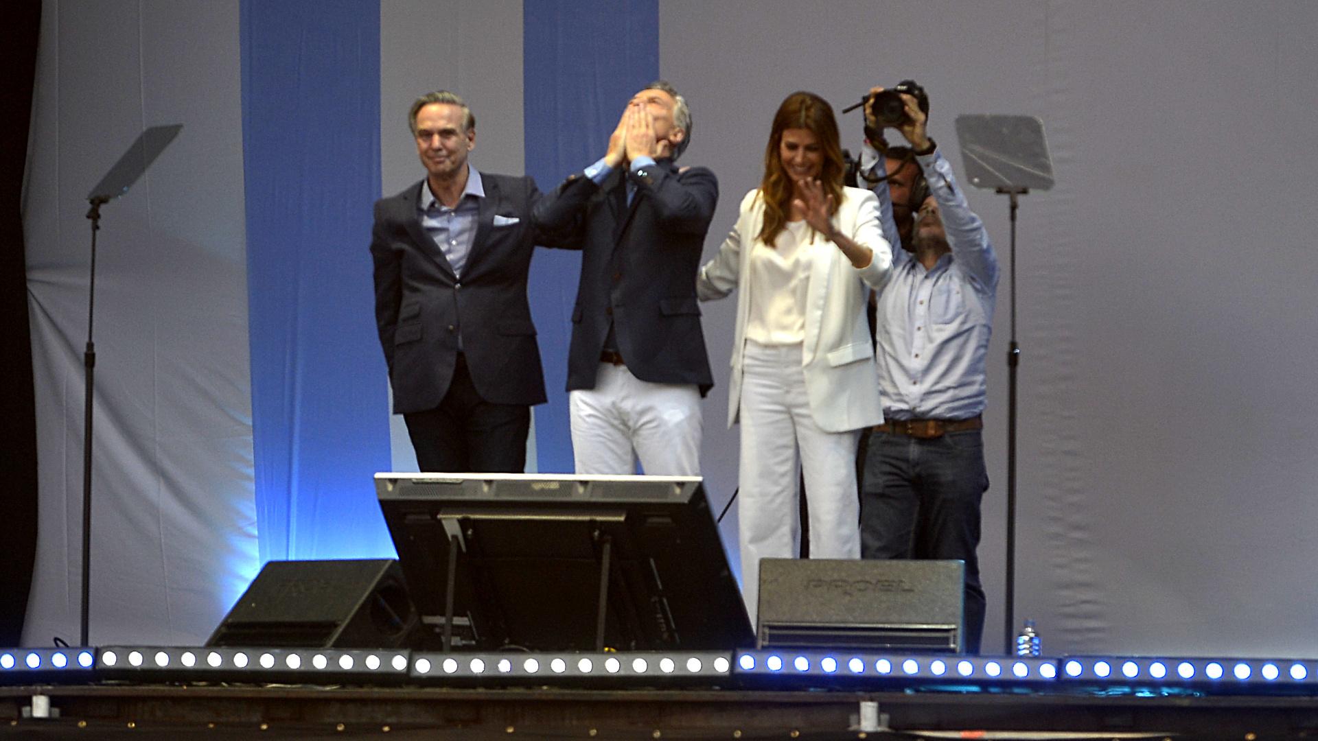 Macri en el placo, flanqueado pro su compañero de fórmula, Miguel Angel Pichetto, y por su esposa, Juliana Awada