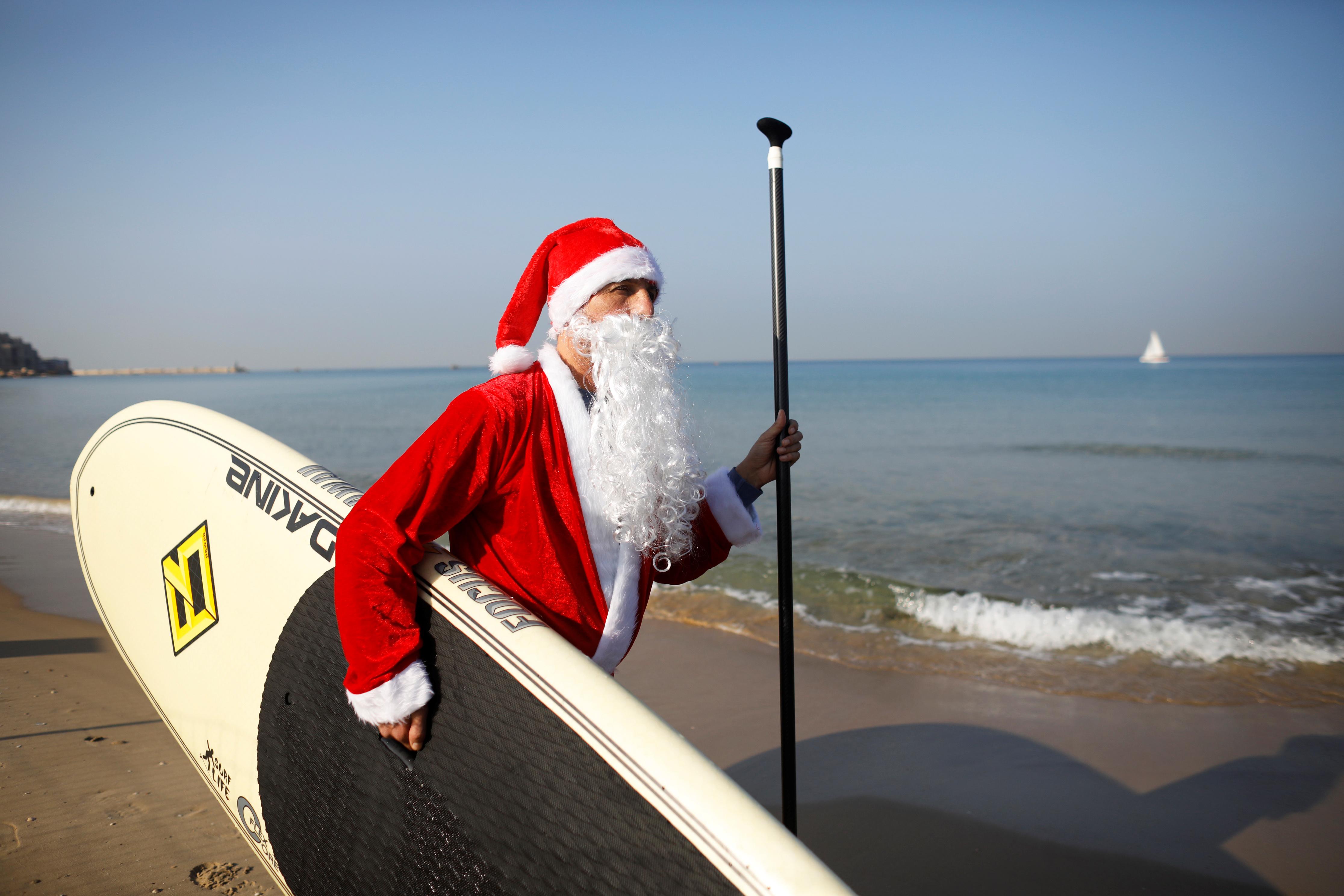 Un hombre vestido con un traje de Santa Claus lleva una tabla de SUP mientras camina por la playa cerca del mar Mediterráneo durante un evento organizado por el municipio de Tel Aviv, frente a la costa de Tel Aviv, Israel, el 22 de diciembre de 2019 (Reuters/ Nir Elias)