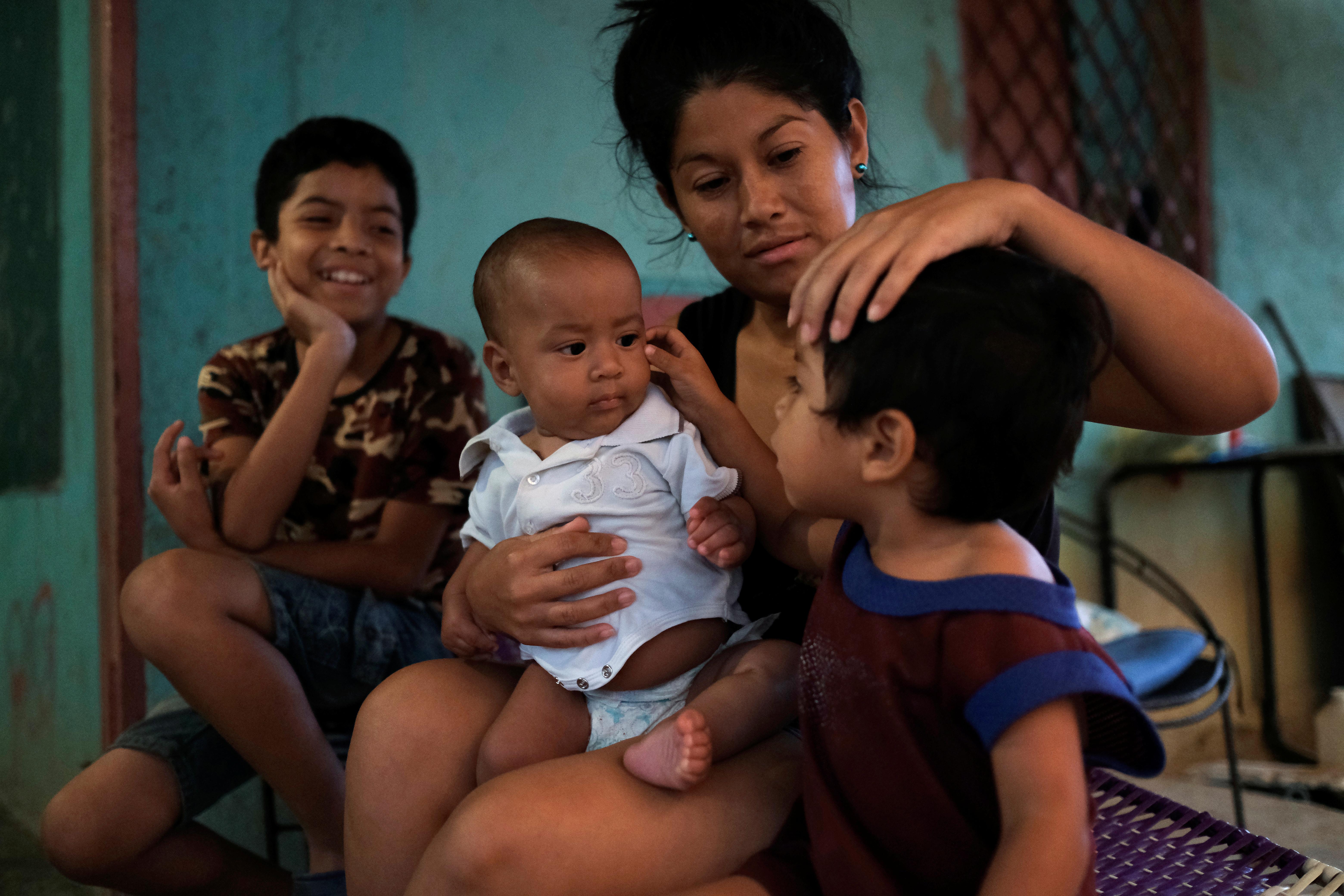 Francys Rivero sostiene a su hijo Kenai, de cinco meses, que se recuperó de la desnutrición, mientras habla con sus hijos Collins, de 11 años, y Enmanuel, de 2, fuera de su casa en Barquisimeto (REUTERS/Carlos Garcia Rawlins)