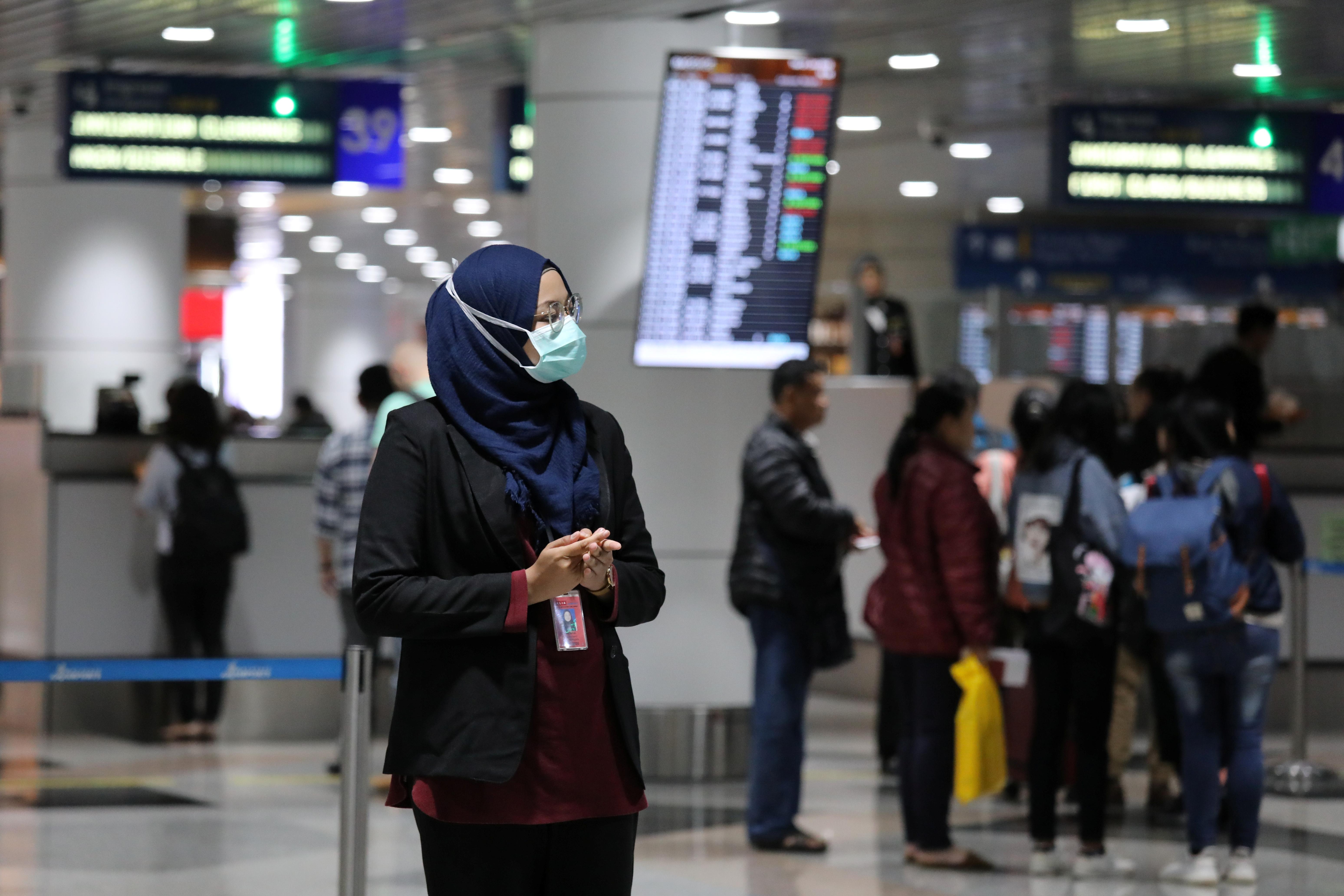 Un oficial de aviación usa una máscara en el aeropuerto internacional de Kuala Lumpur en Sepang, Malasia, el 21 de enero de 2020. REUTERS / Lim Huey Teng