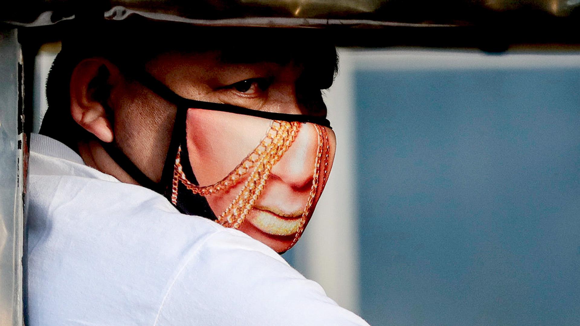 Un hombre usa una máscara protectora con un diseño de personaje dentro de un taxi colectivo, luego de dos casos confirmados de coronavirus en el país, en la ciudad filipina de Quezon (REUTERS / Eloisa Lopez)
