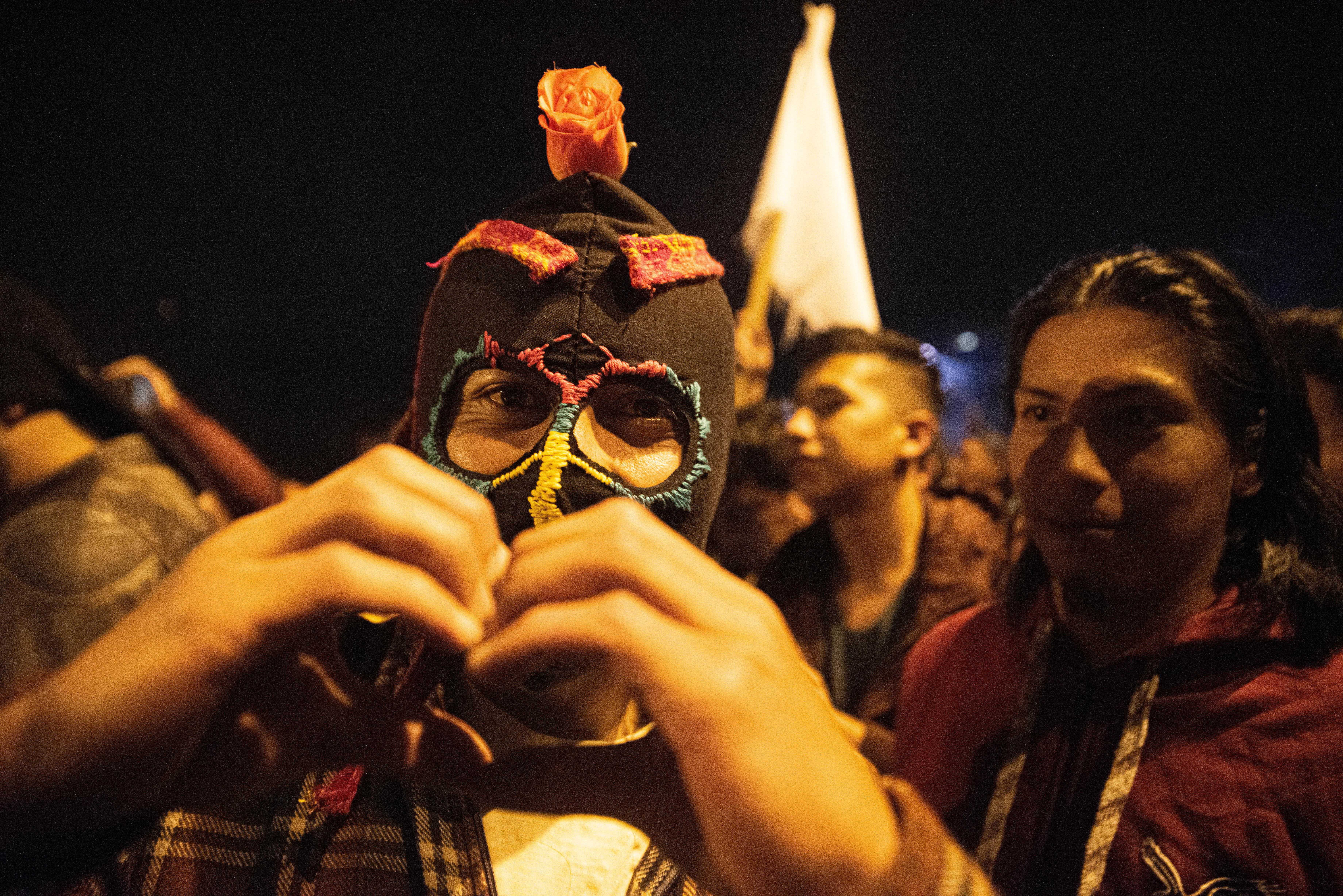 Un hombre con una mascara en los festejos del domingo por la noche hace una forma de corazón. Los manifestantes pedían