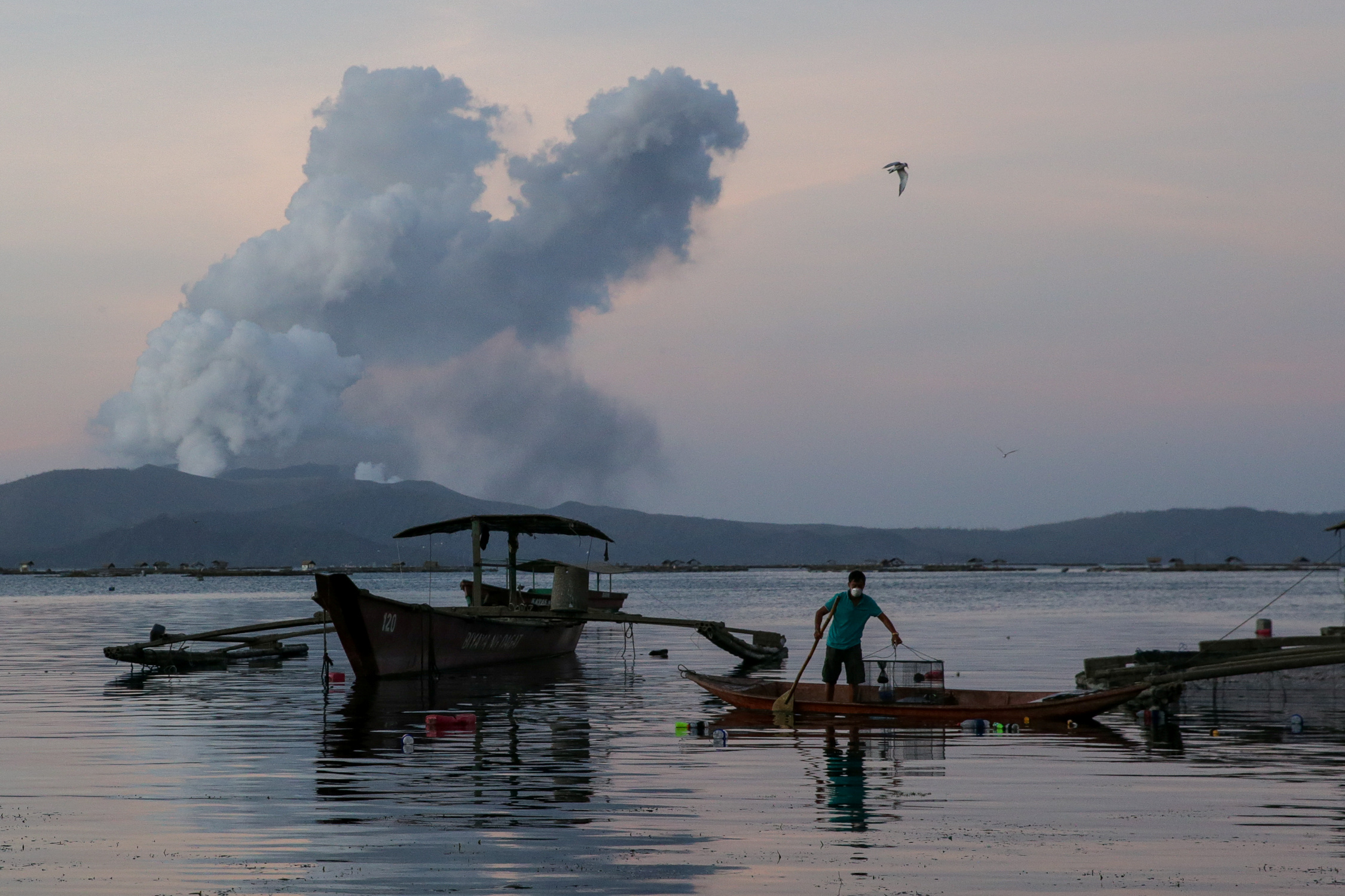 Un pescador captura peces mientras el Volcán Taal se erra continuamente en Talisay, Batangas, Filipinas, el 16 de enero de 2020. REUTERS / Eloisa Lopez