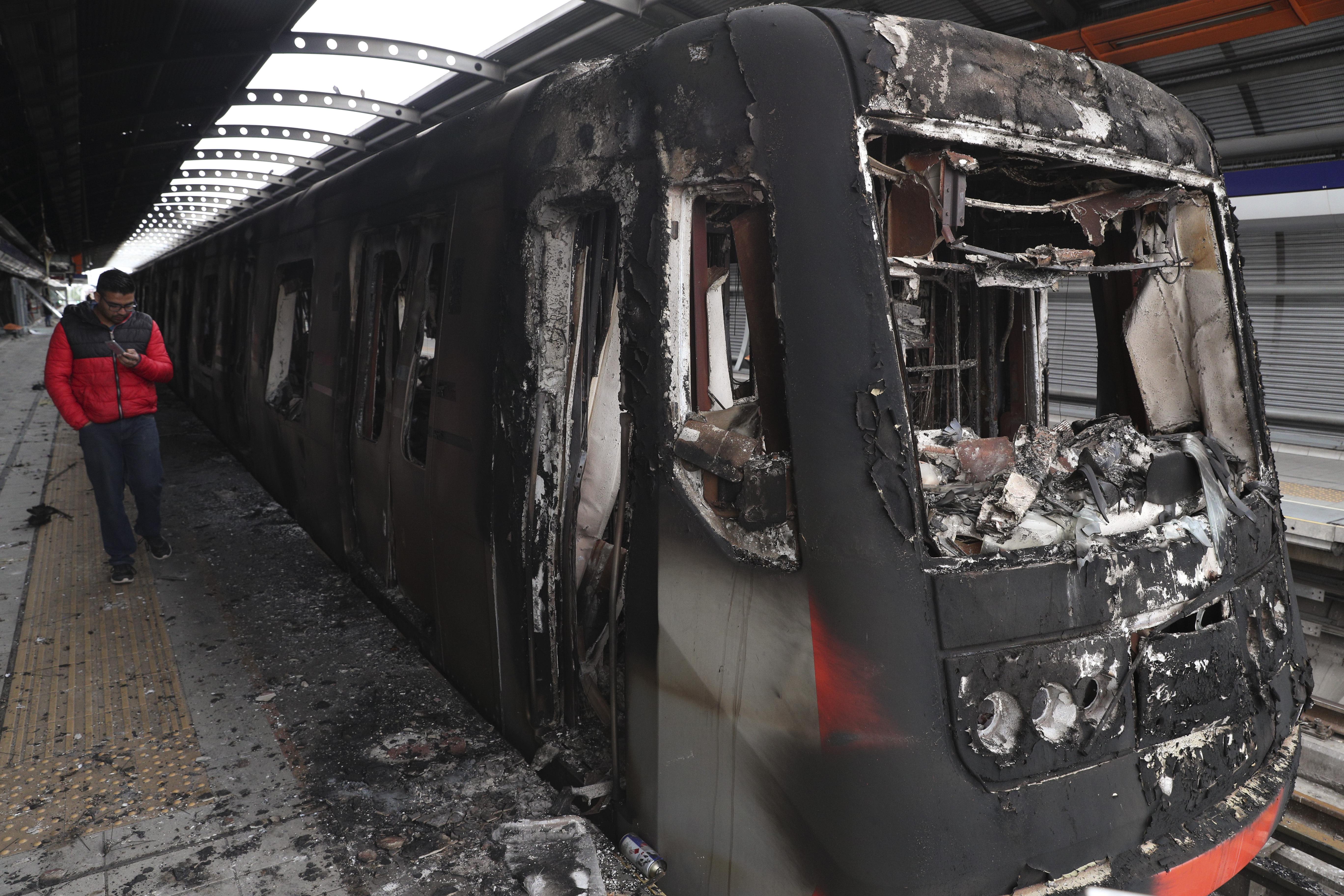 Un tren ennegrecido por el fuego tras el ataque de manifestantes en la estación Elisa Correa