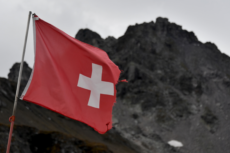 Una bandera nacional suiza ondea durante una ceremonia para conmemorar la 'muerte' del glaciar Pizol (Pizolgletscher). (Foto por Fabrice COFFRINI / AFP)