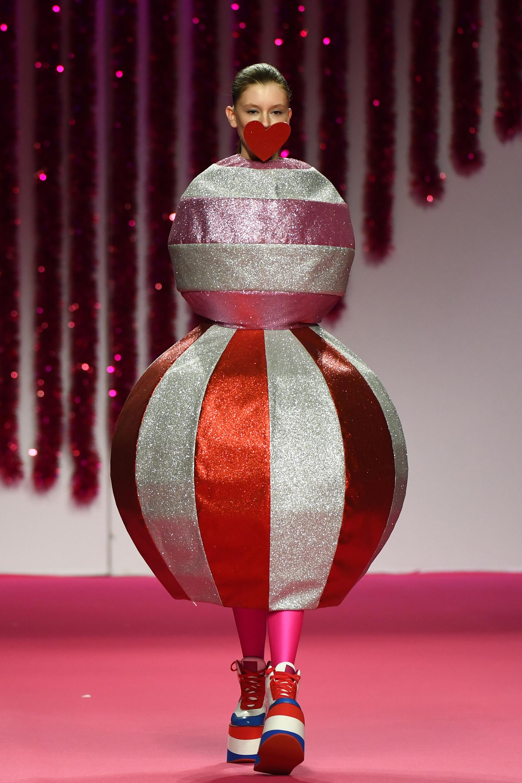 Un particular diseño de Ágatha Ruiz de la Prada: dos esferas metalizadas de glitter rayadas con mega plataformas. El estilismo del desfile consistía en tapar la boca de las modelos con corazones de cartón en rojo